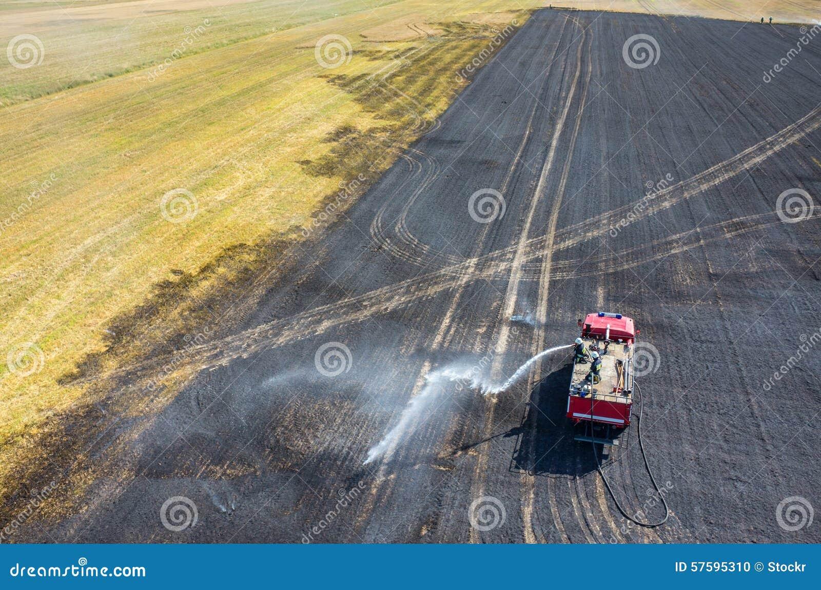Тележка пожарного работая на поле на огне