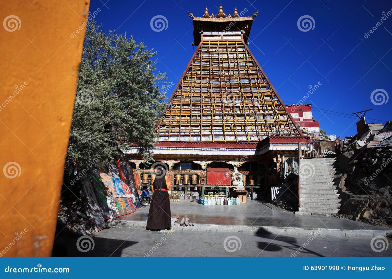 Тибетская женщина молила под пагодой 10 тысяч Будды