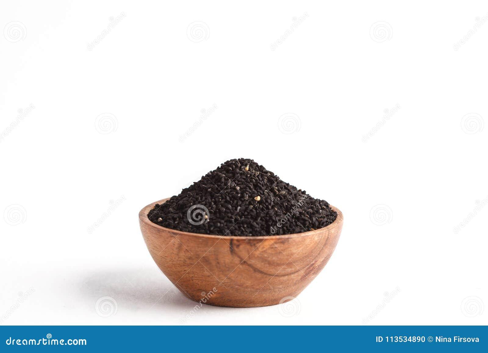 Тимон Nigella sativa или черный в деревянном шаре на белой предпосылке