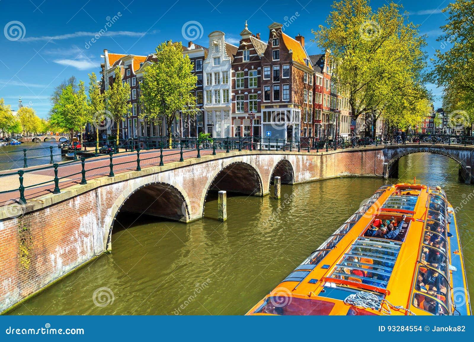 Типичные каналы Амстердама с мостами и красочной шлюпкой, Нидерландами, Европой