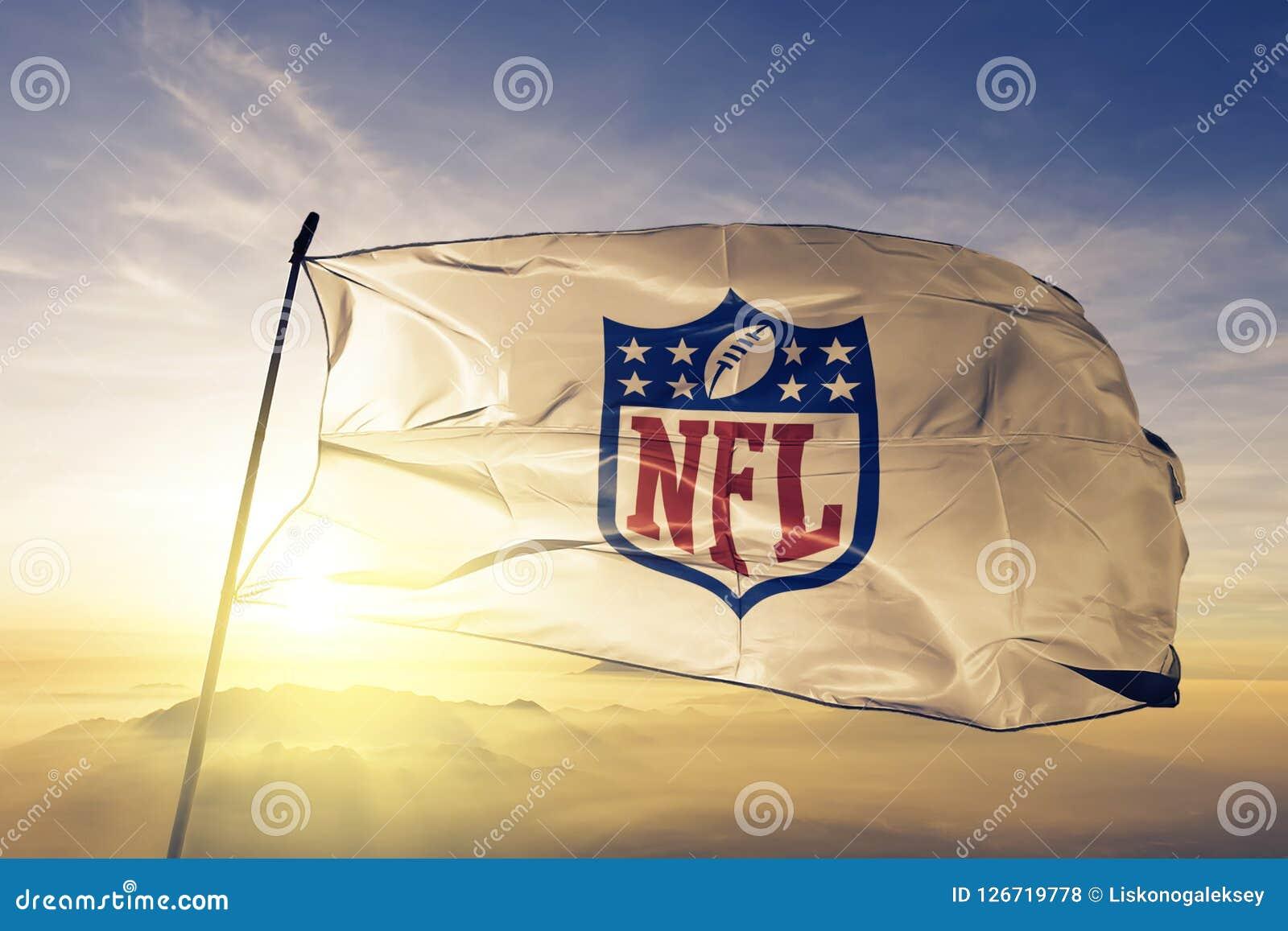Ткань ткани ткани флага логотипа Профессиональной лиги американского футбола NFL развевая на верхнем тумане тумана восхода солнца