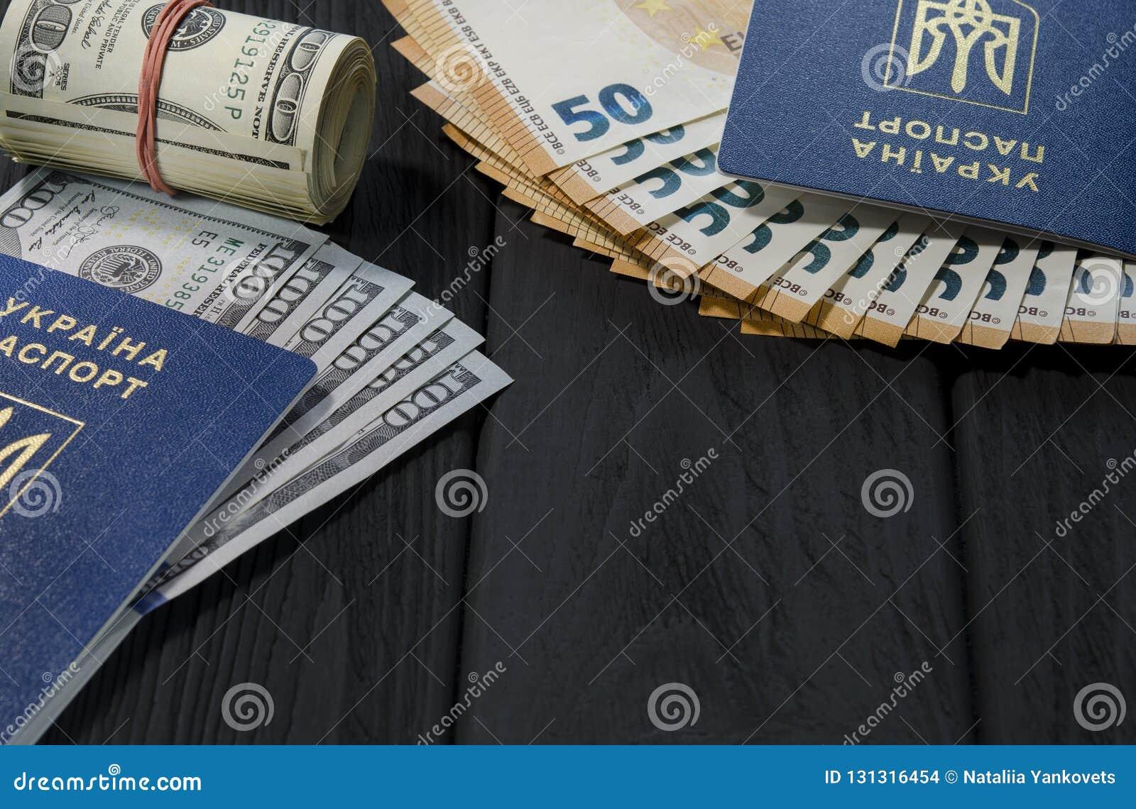 Толстый крен старых 100 долларовых банкнот связанных с красной круглой резинкой лежит рядом с биометрическими паспортами граждан