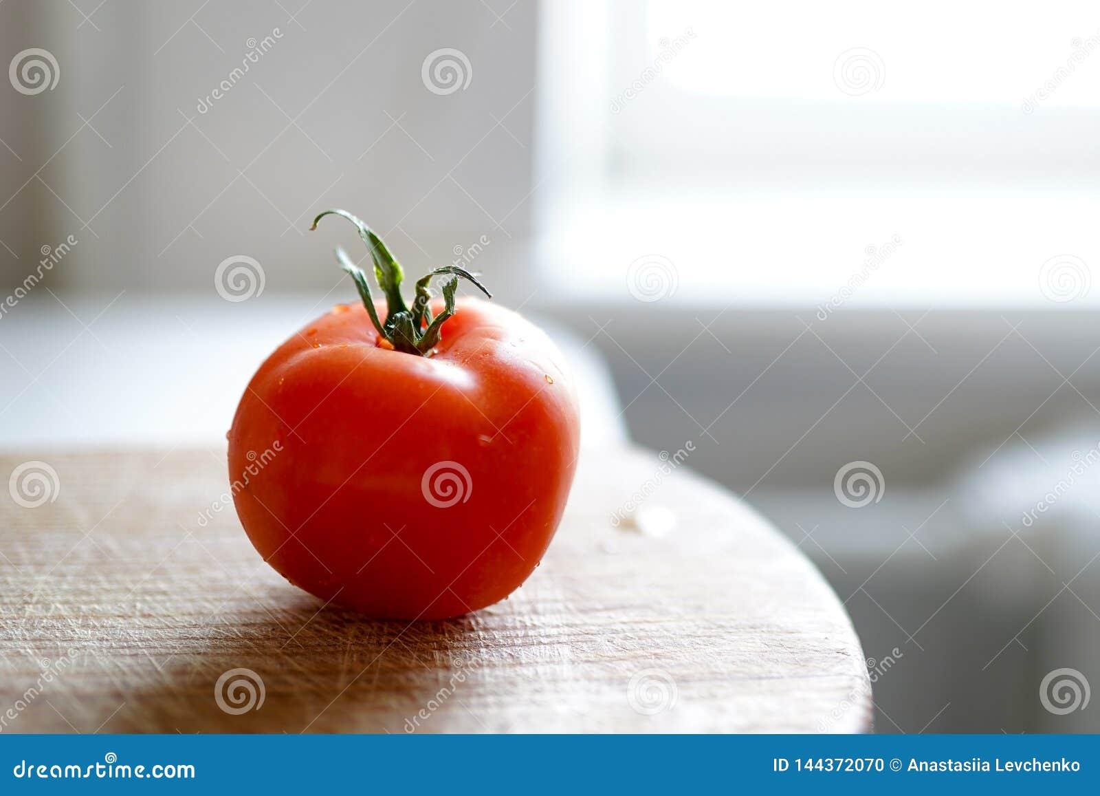 Томат на доске вырезывания деревянной на белой предпосылке r Свежий томат wased для варить Томат с капельками