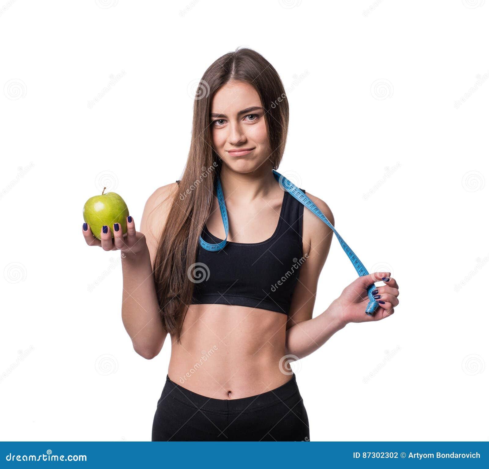 Тонкая и здоровая молодая женщина держа ленту измерения и яблоко изолированное на белой предпосылке Потеря веса и концепция диеты