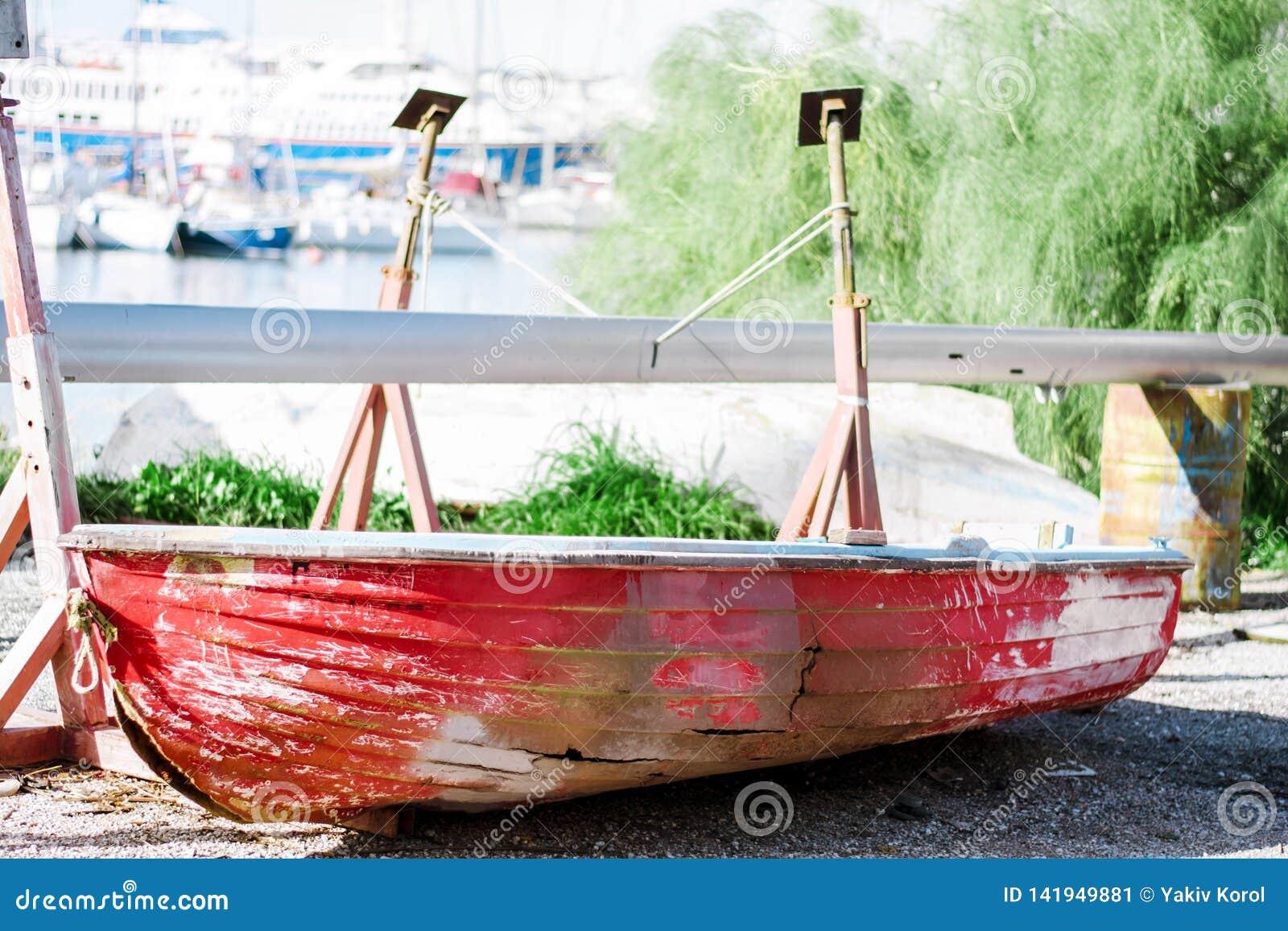 Тонуть красная шлюпка с отверстиями в бортовом ремонте в сухом доке Афиныы, Греция