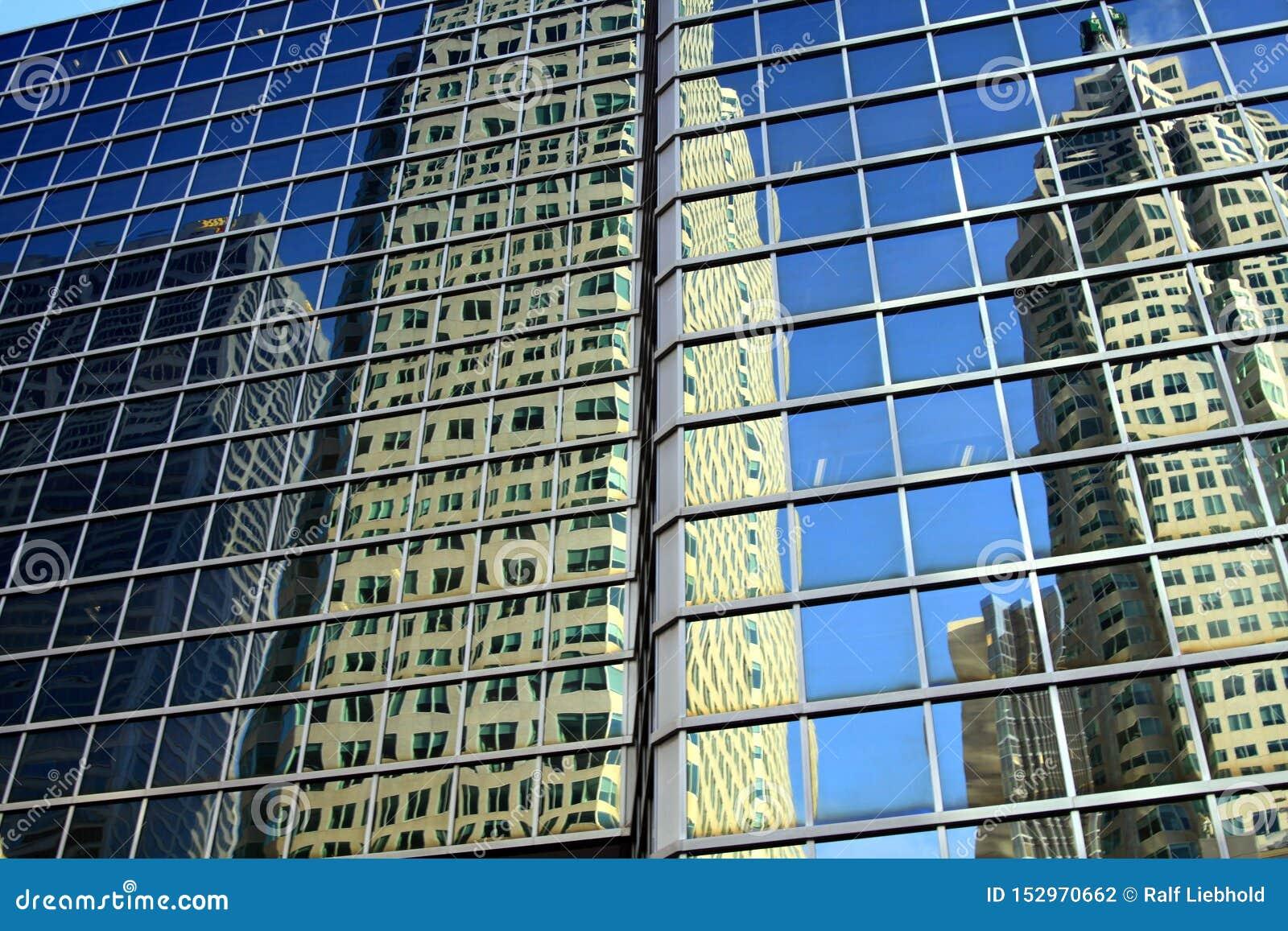 ТОРОНТО, КАНАДА - 8-ОЕ ЯНВАРЯ 2012: Небоскребы и безоблачное голубое небо отражая в стеклянном фасаде