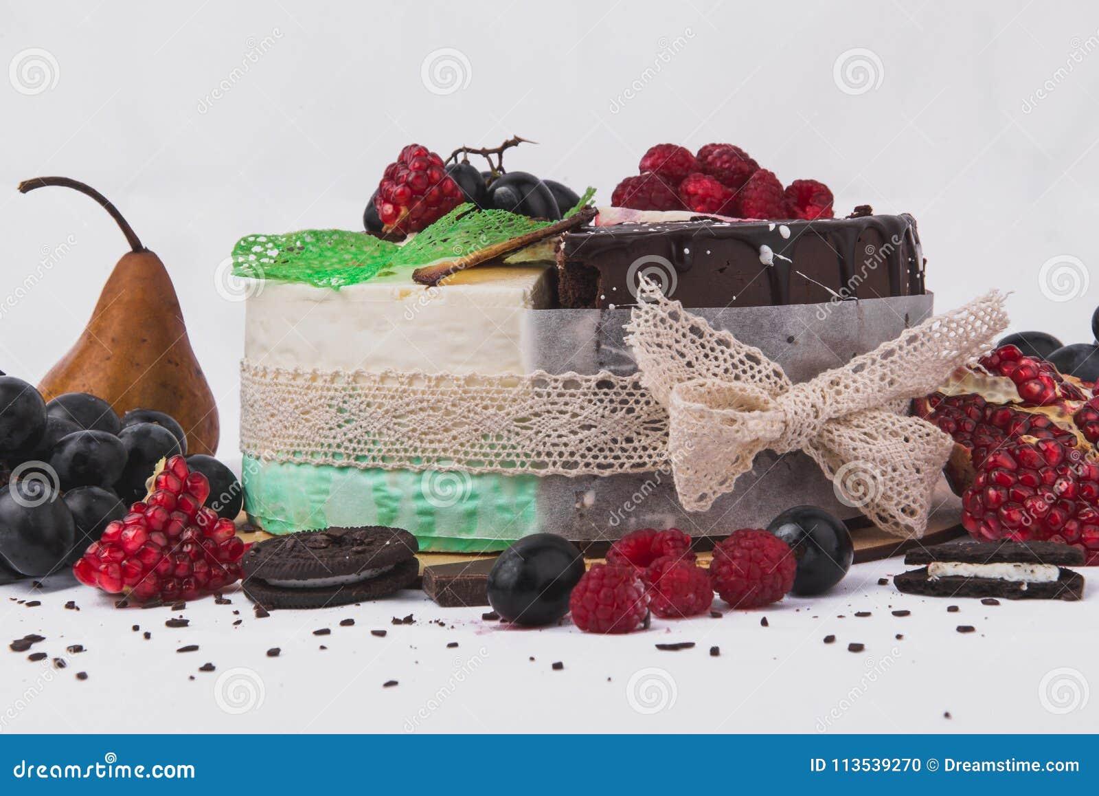 Торты украшенные с полениками, грушами, печеньями, виноградинами, гранатовыми деревьями на белой предпосылке