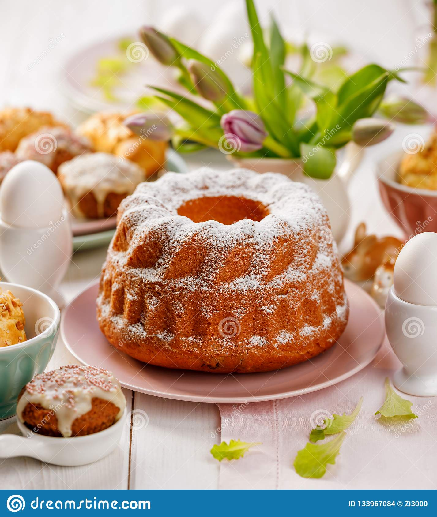 Торт дрожжей пасхи взбрызнутый с напудренным сахаром на таблице праздника