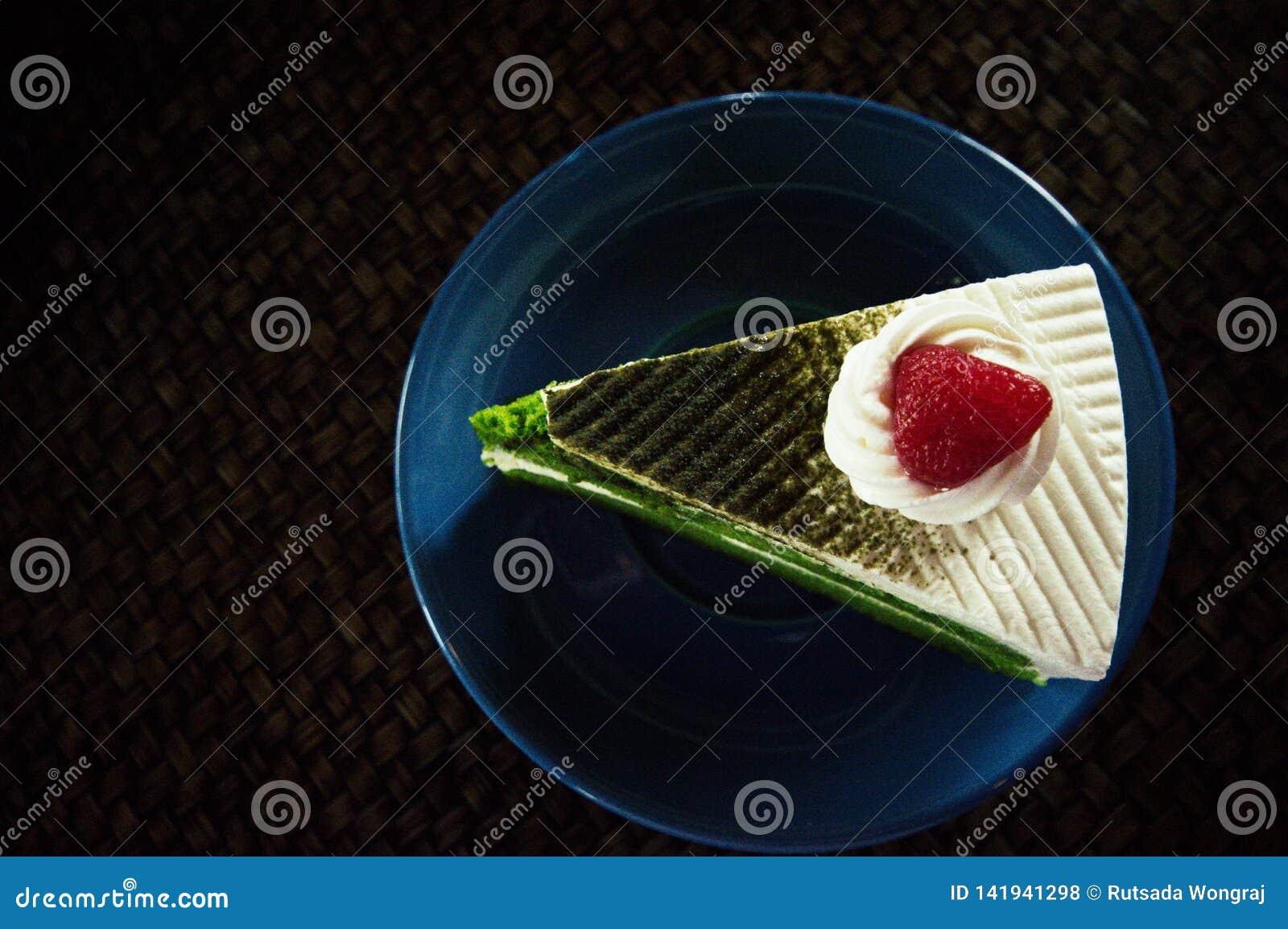 Торт зеленого чая помещенный на голубой плите