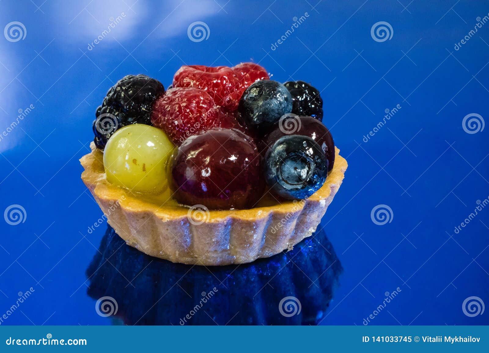 Торт со свежими био плодами, виноградинами, полениками, ежевиками, фото взгляда со стороны, предпосылкой зеркала голубой