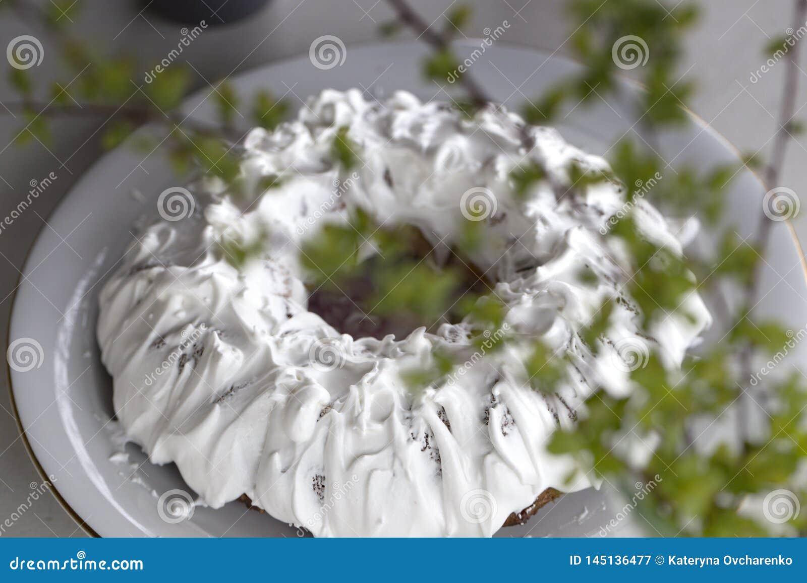 Домодельный торт с чаем Торт с замороженностью сахара Домодельный торт в форме кольца с чашками чаю или кофе на белой таблице