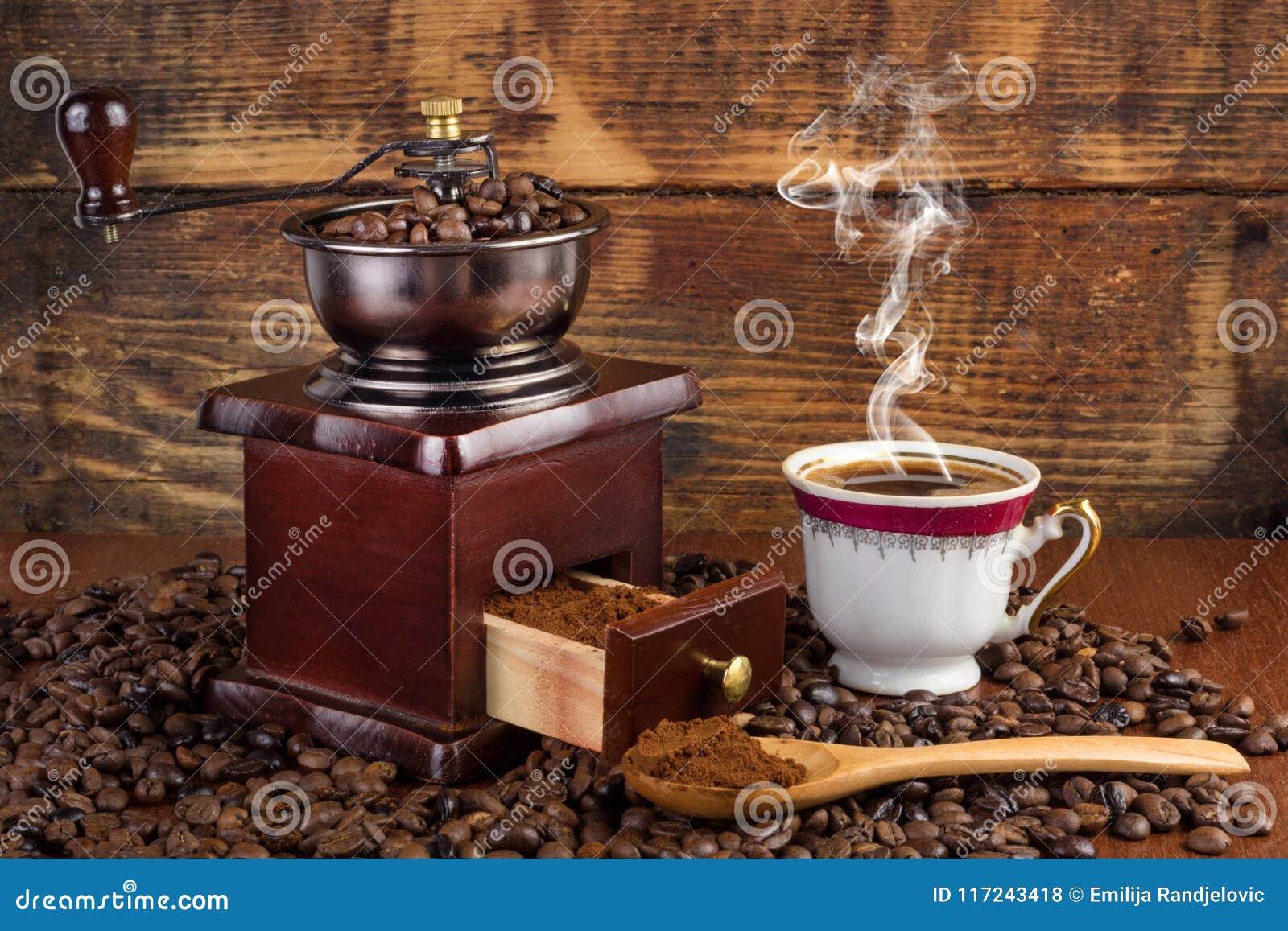 Точильщик мельницы кофе и чашка кофе с дымом и деревянная ложка на ретро предпосылке