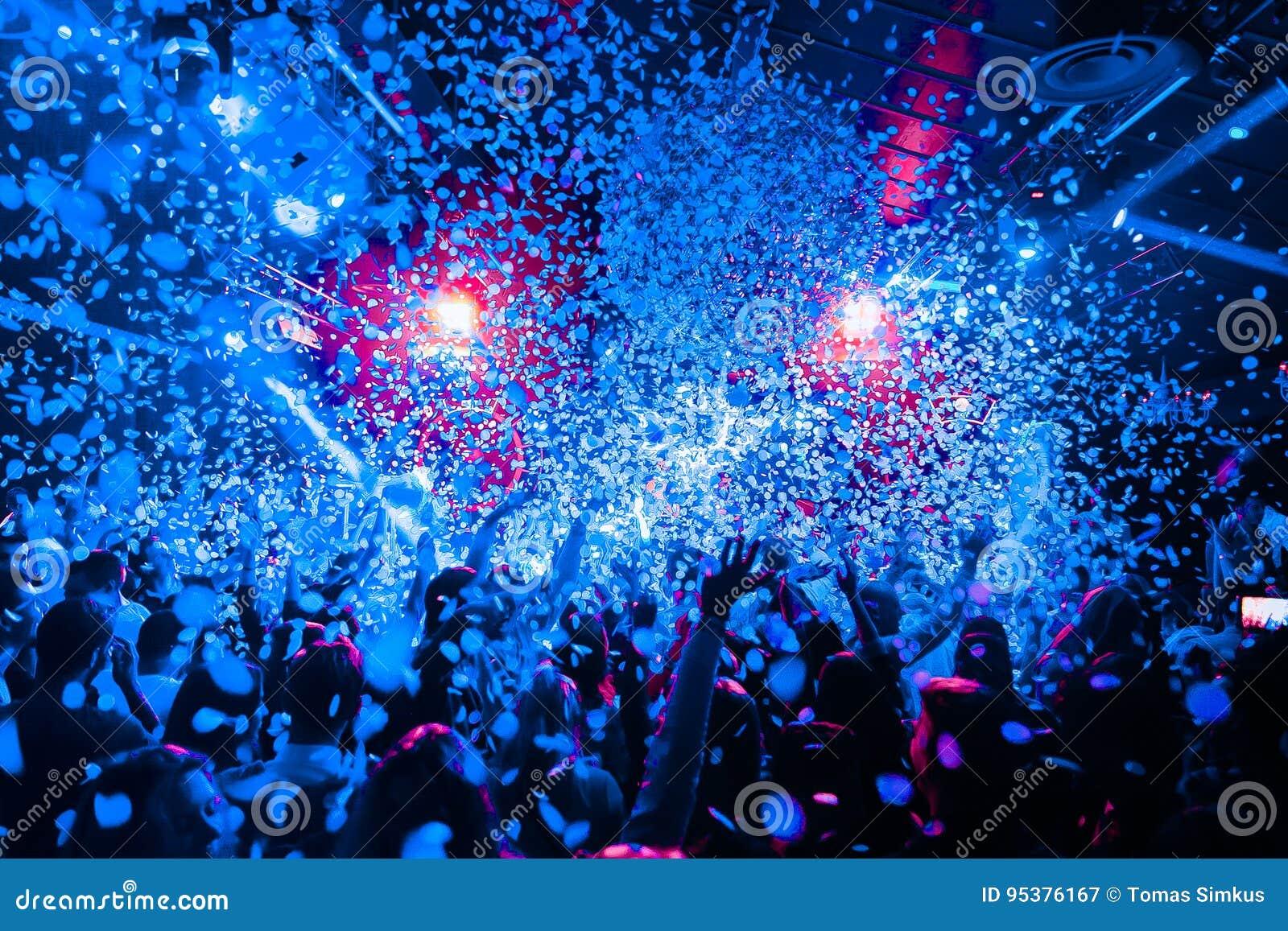 Толпа силуэта ночного клуба вручает вверх на этапе пара confetti
