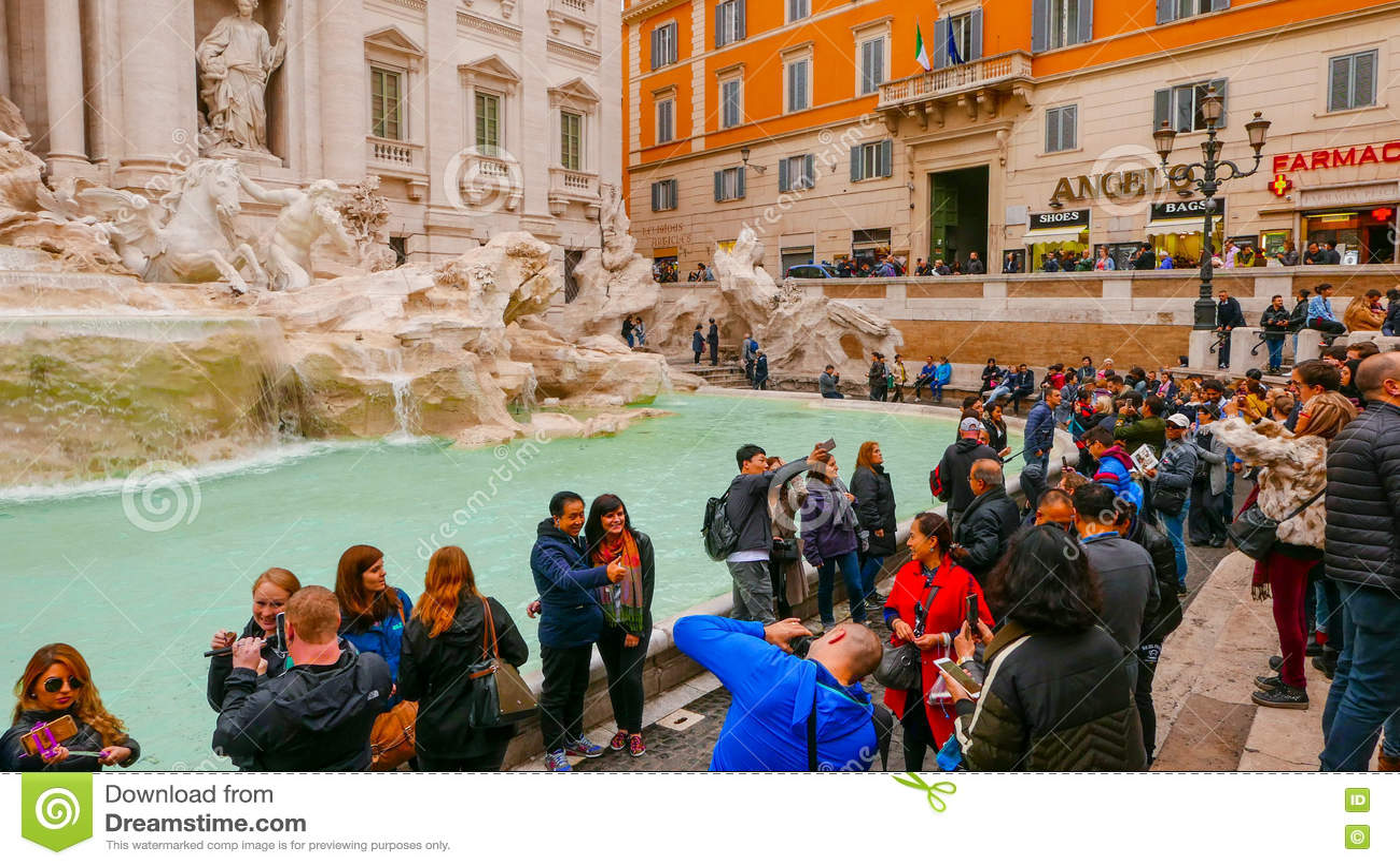 Толпа туристов посещая фонтаны Trevi в историческом районе Рима