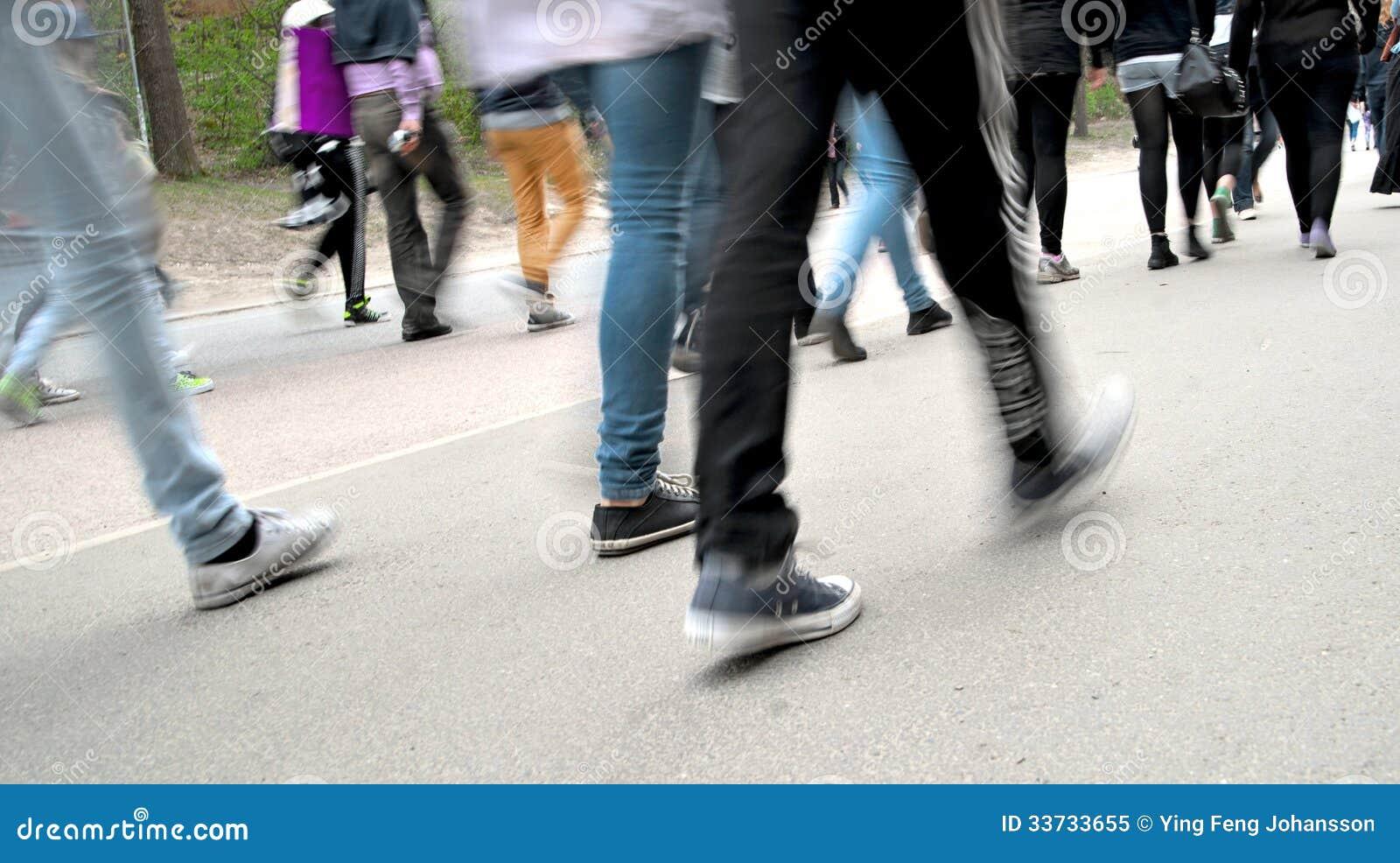 Толпа людей идя на дорогу