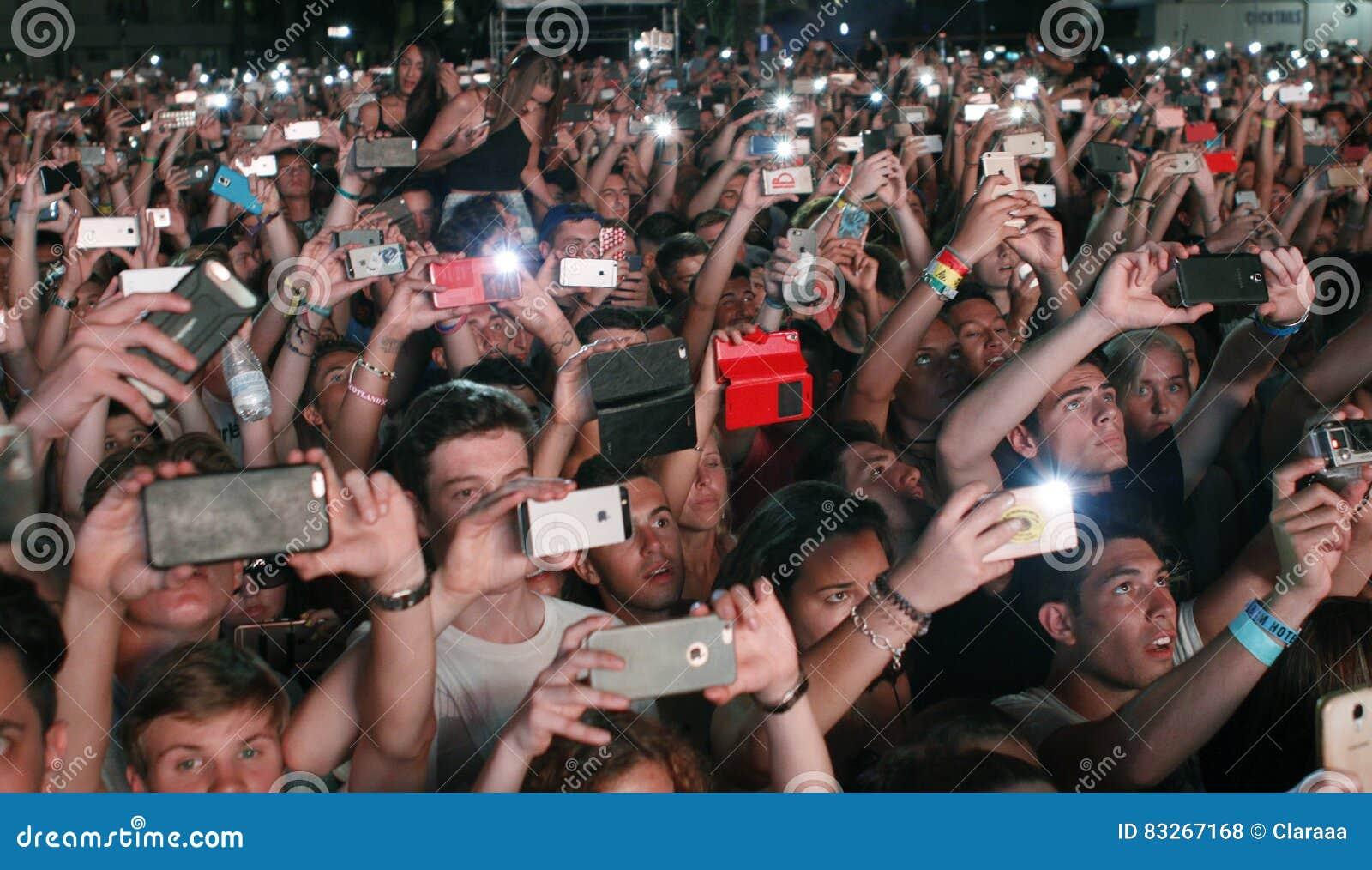 Толпа людей принимая фото с телефоном