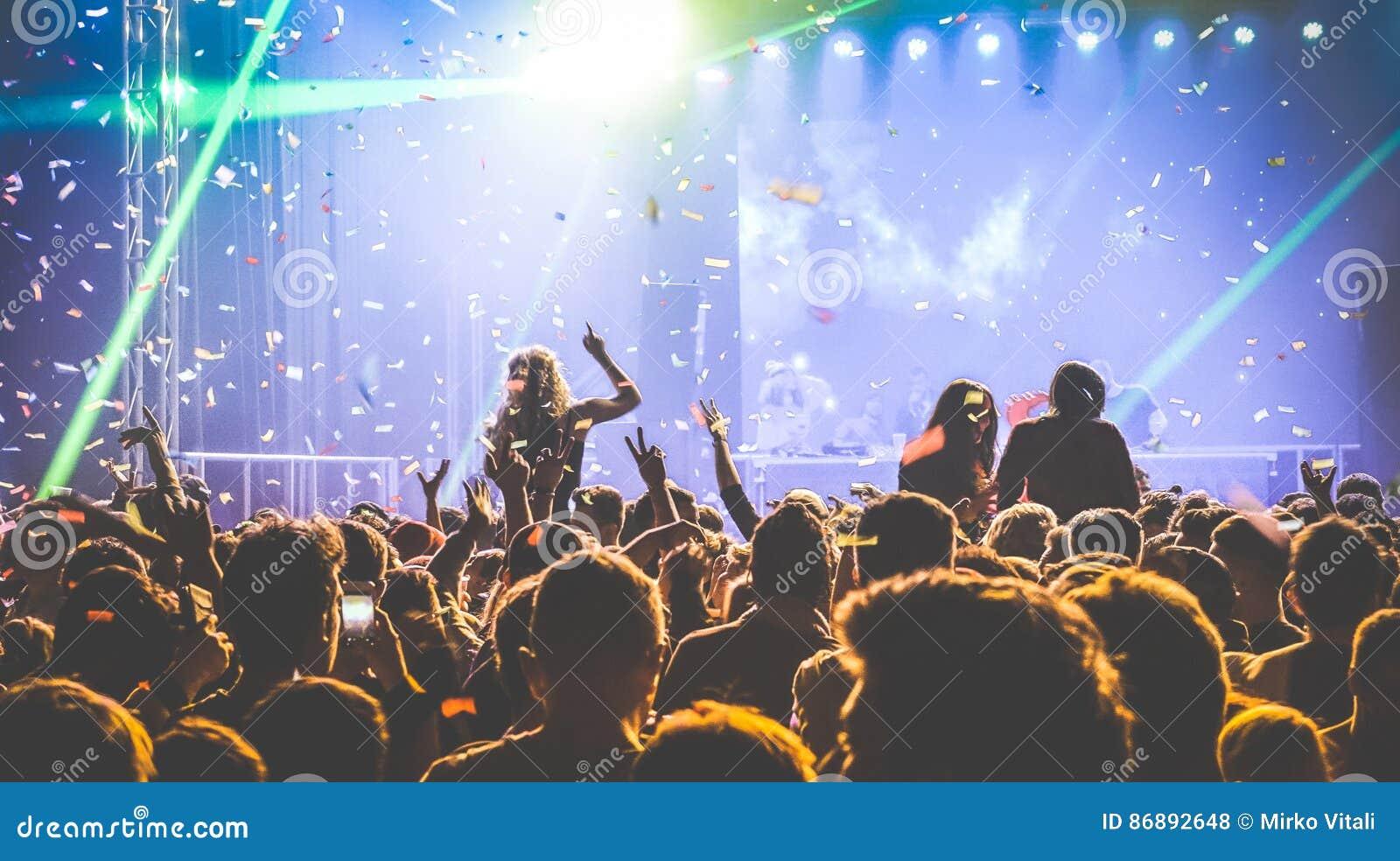 Толпа людей танцуя на ночном клубе - событии в реальном маштабе времени фестиваля концерта