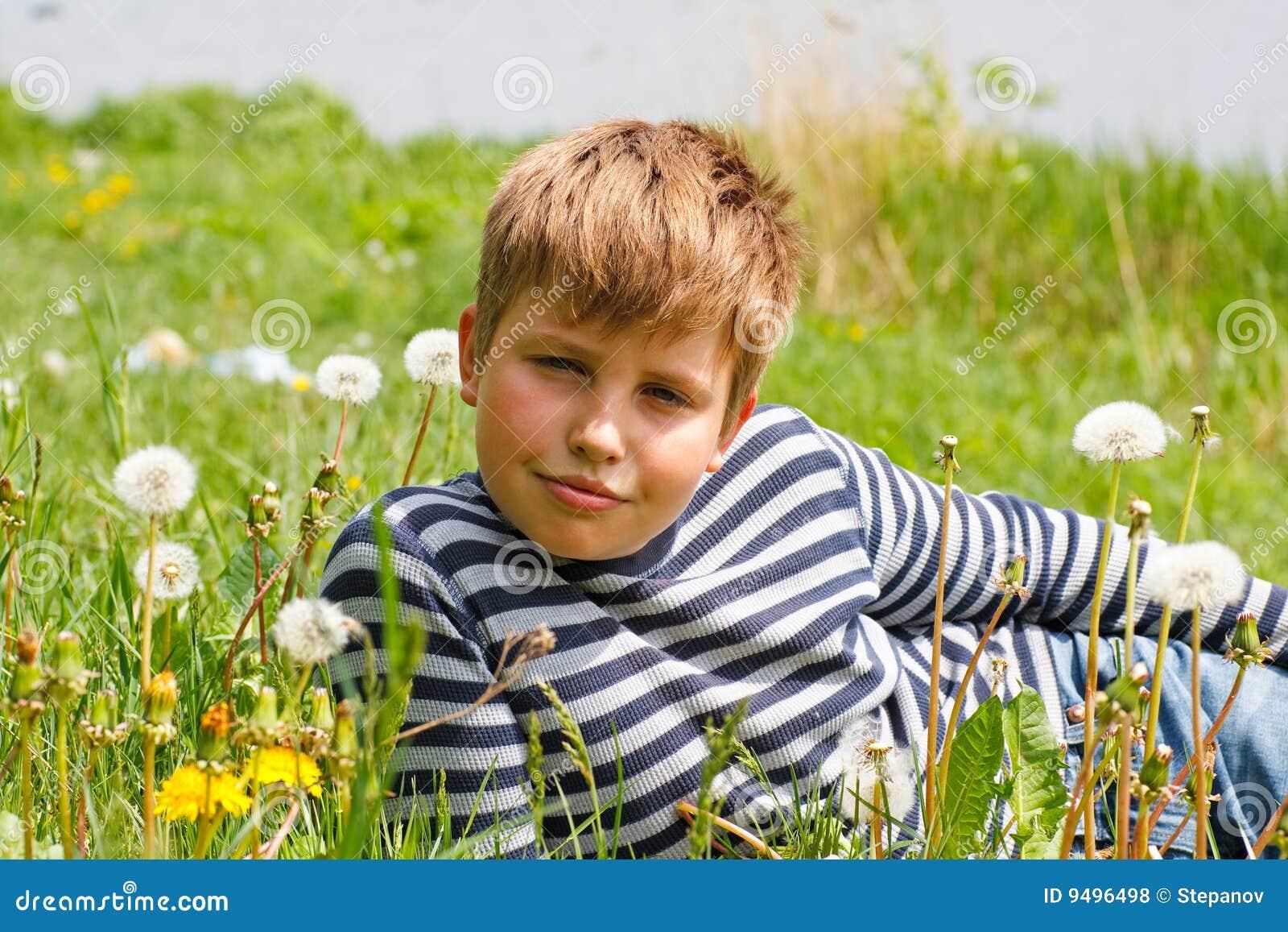 трава мальчика лежит около реки