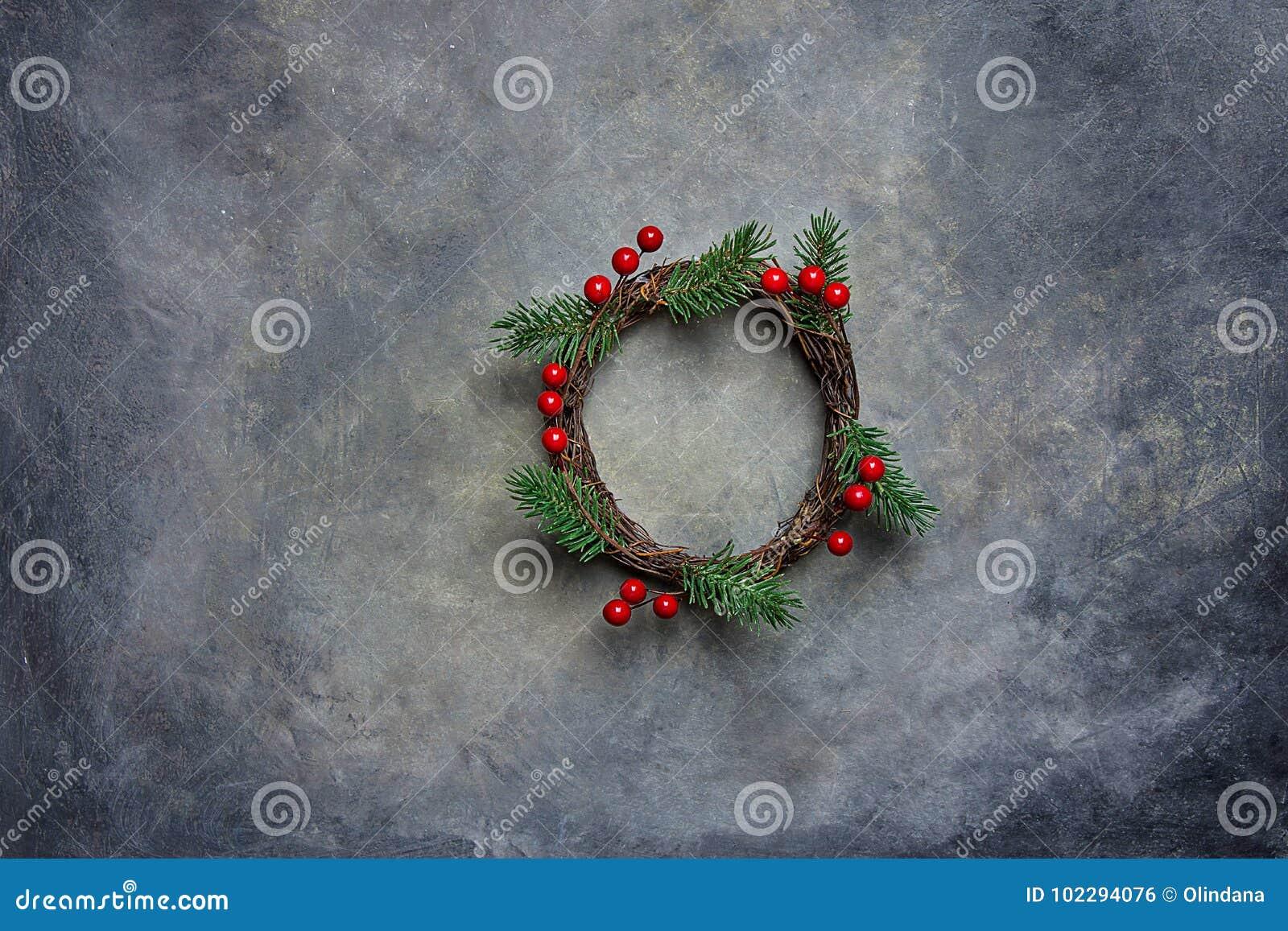 Традиционные Handmade ягоды падуба хворостин ветвей ели зеленого цвета венка рождества на Grungy темной каменной предпосылке Взгл