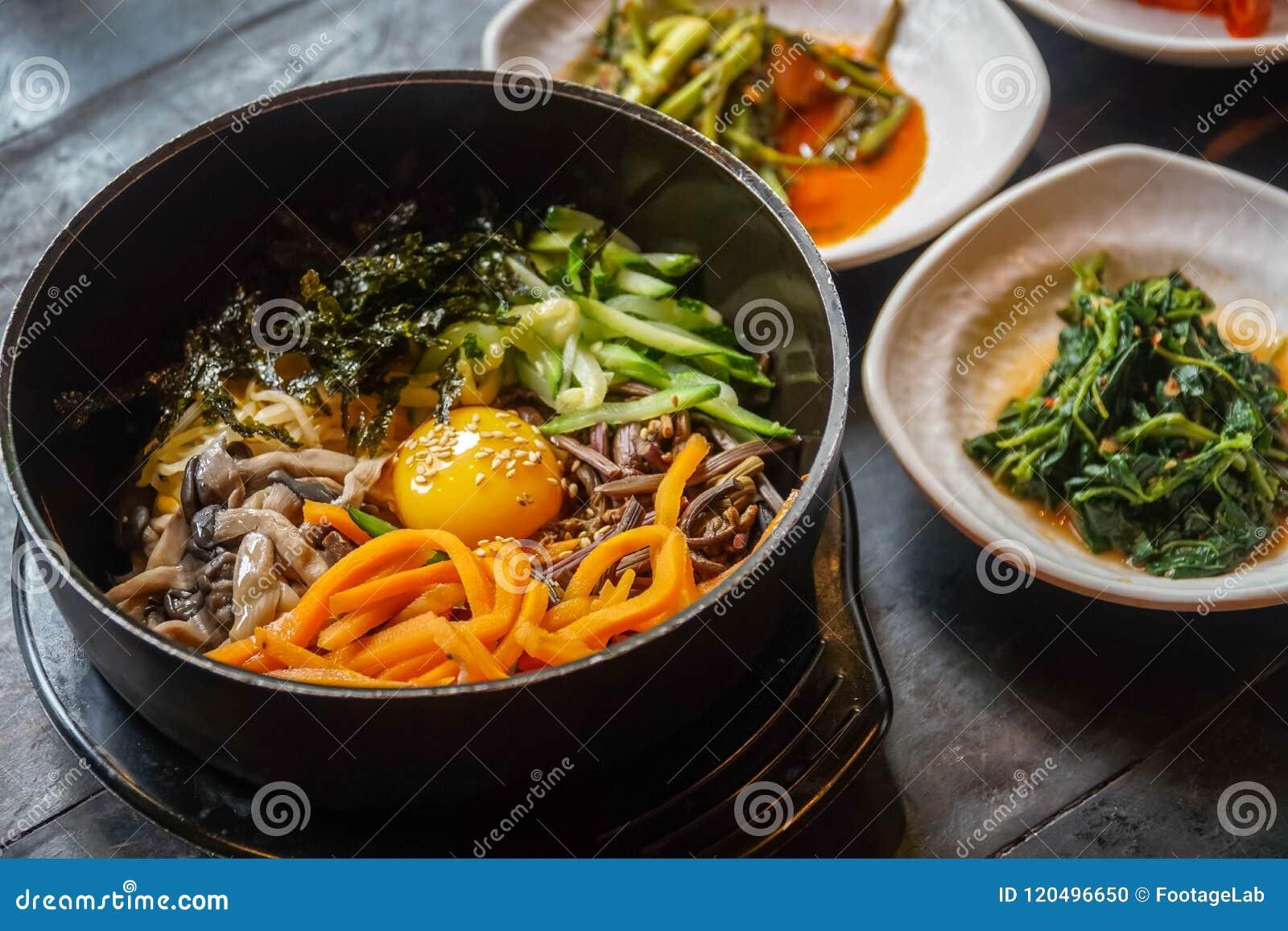 Традиционный корейский Bibimbap блюда, который служат вместе с малыми гарнирами Clled Banchan Азиатская подлинная кухня