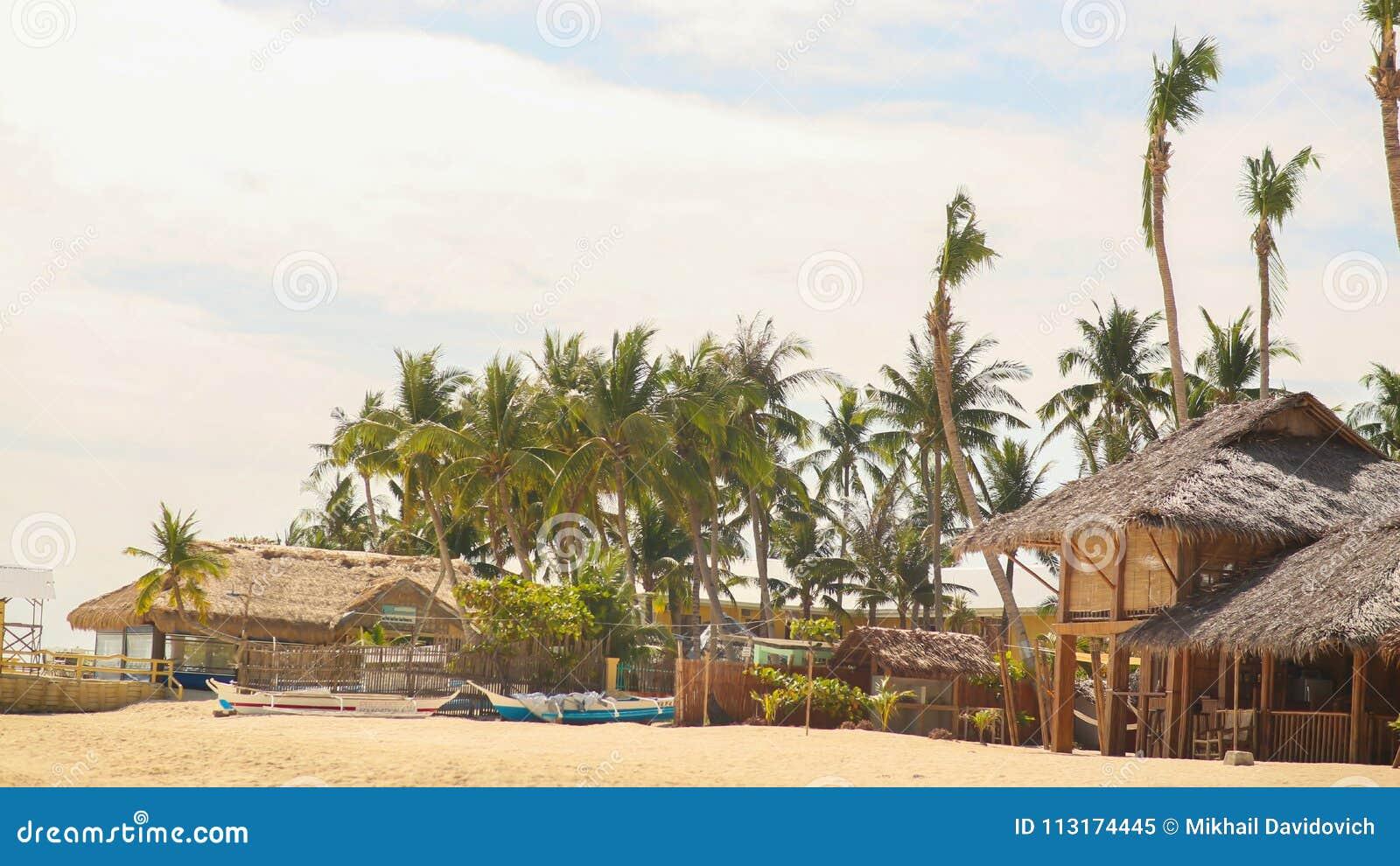Традиционный рыбацкий поселок среди пальм на песочном побережье Филиппинах
