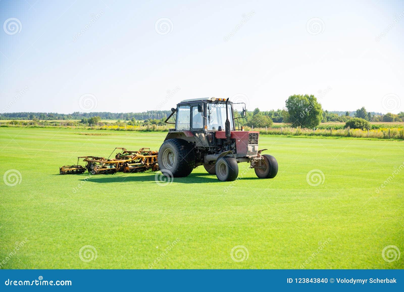 Трактор с соплом для заботы лужайки поля для поло лошади в работе Трава выключения принимает от механически частей никакого