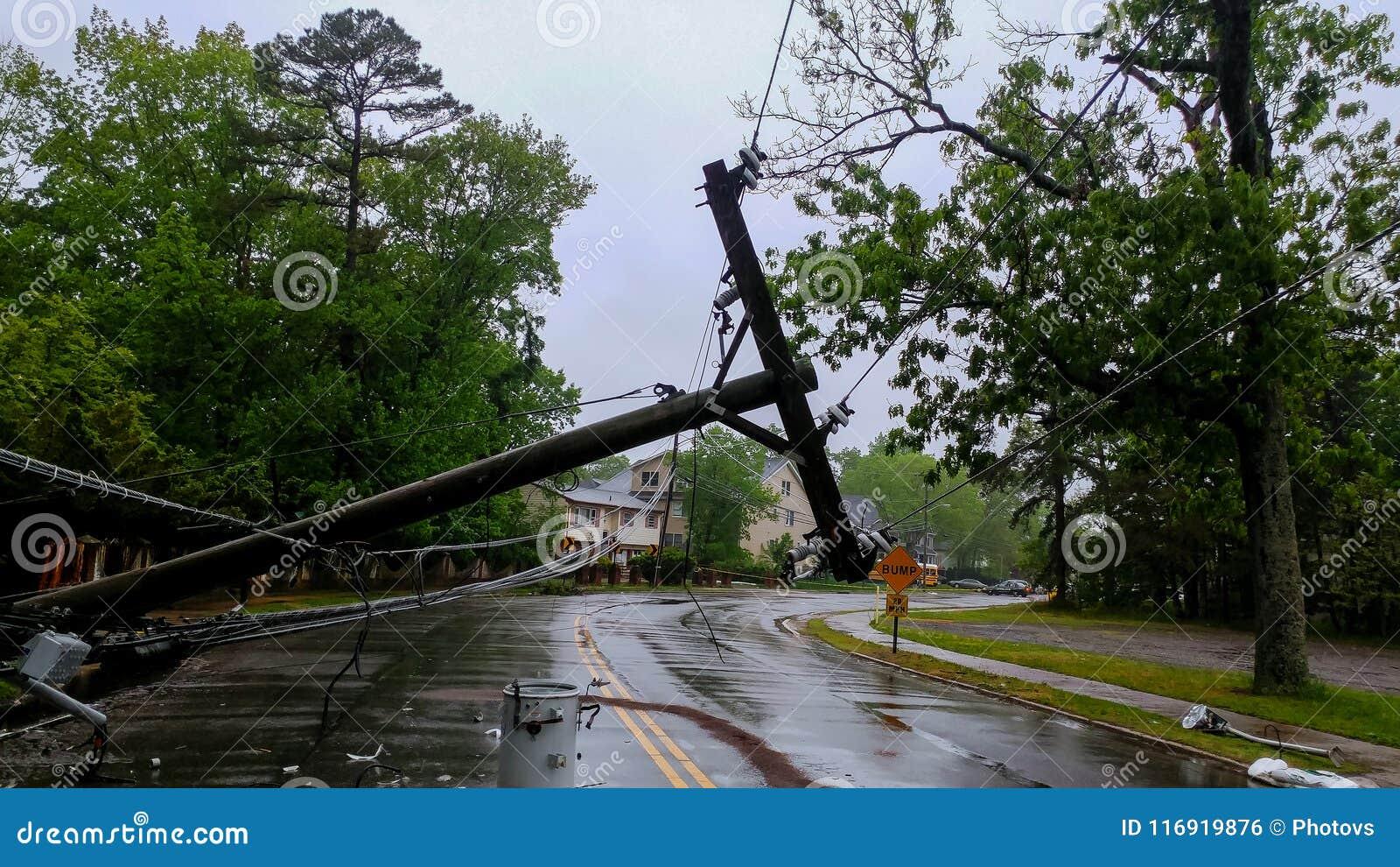 трансформатор на поляке и дереве кладя через линии электропередач над дорогой после урагана двинул поперек