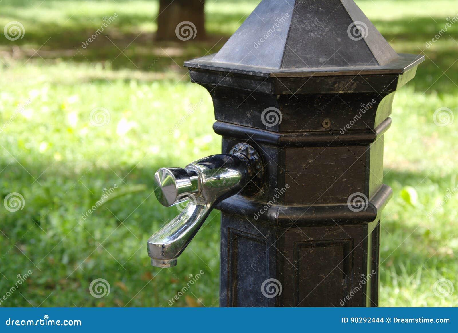 Традиционный кран воды из городского водопровода с питьевой водой в парке