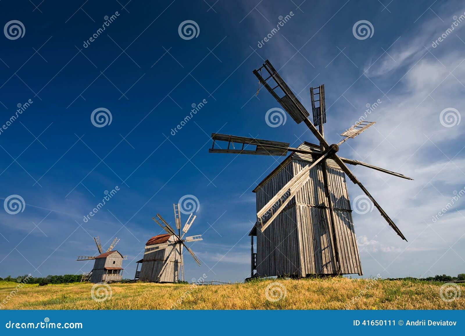 3 традиционных ветрянки на сельской местности на заходе солнца
