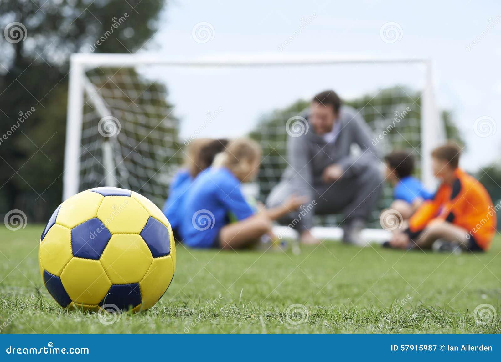 Тренер и команда обсуждая тактик футбола с шариком в Foregroun