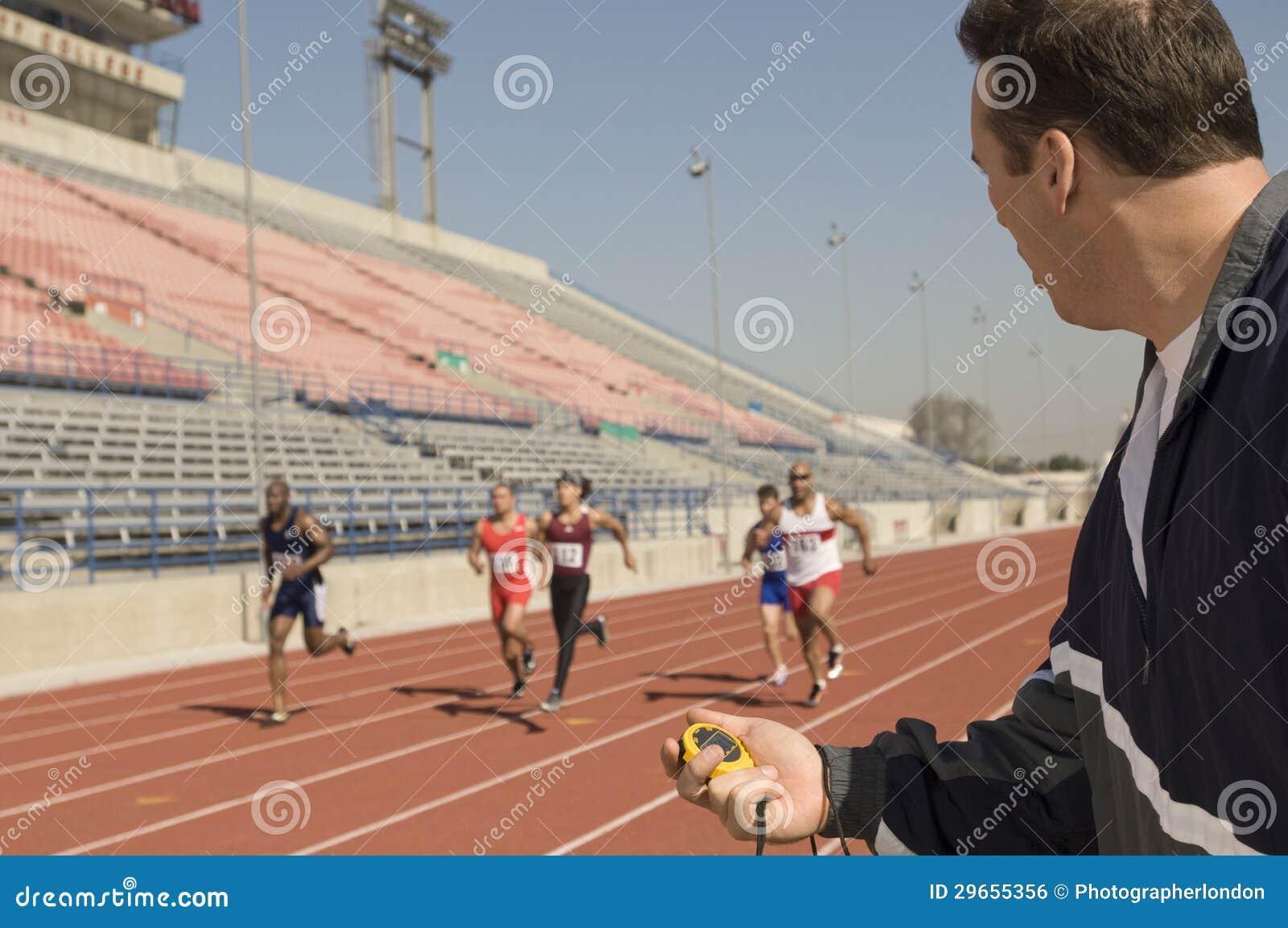 Тренер с секундомером пока спортсмены участвуя в гонке в беговой дорожке
