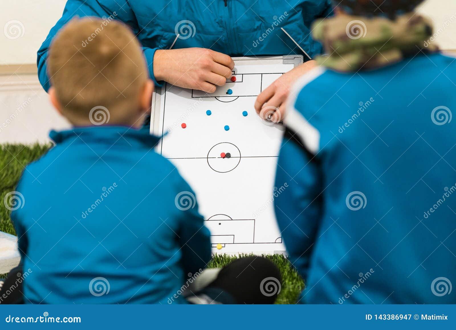 Тренер футбола молодости тренируя детей Тактик тренеров футболистов мальчиков слушая и мотивационная беседа