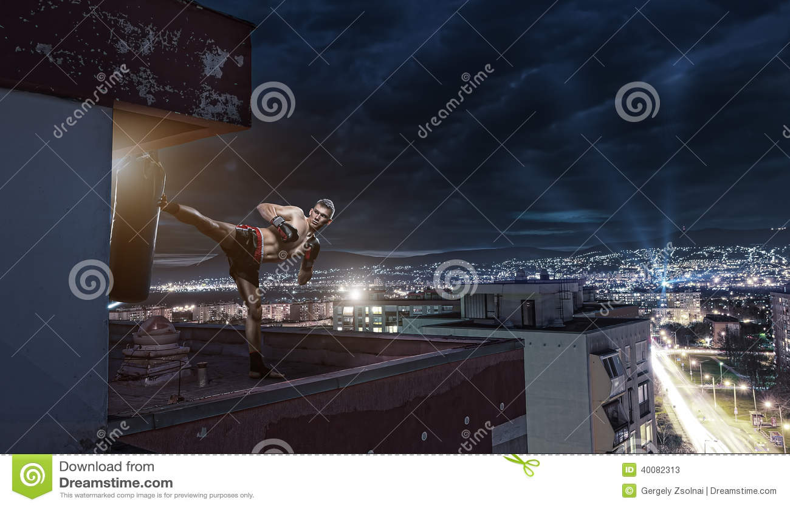 Тренировка бокса молодого человека, na górze дома над городом