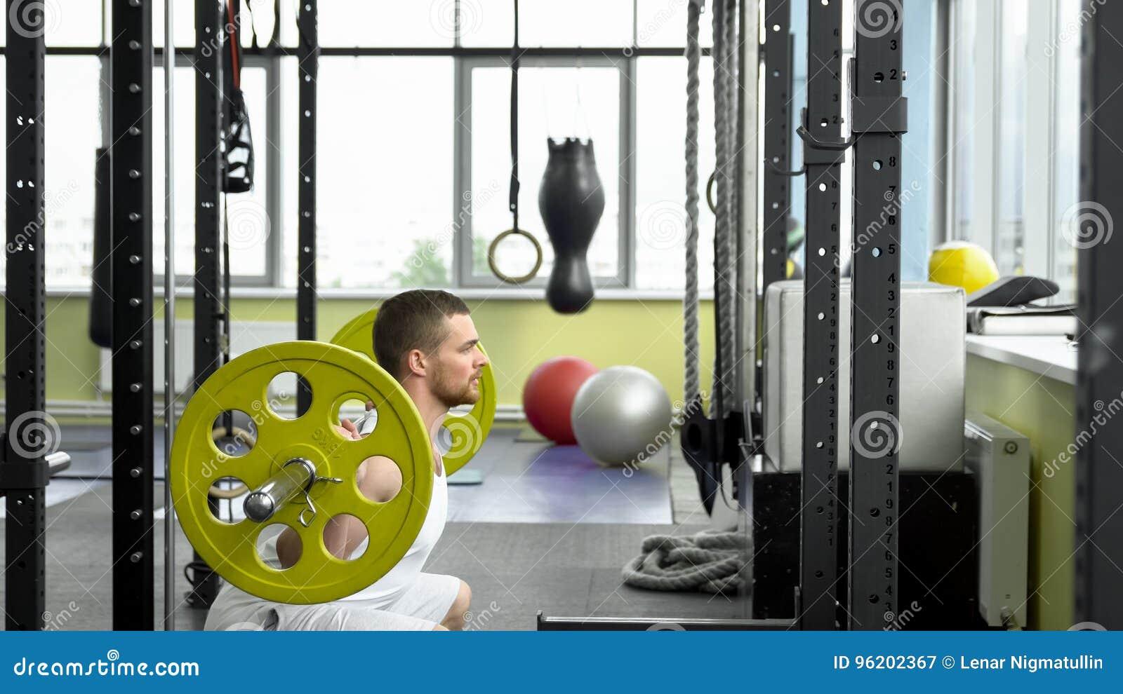 Тренировка прочности в спортзале парень делая сидения на корточках с штангой культурист делая тренировку с штангой Взгляд со стор