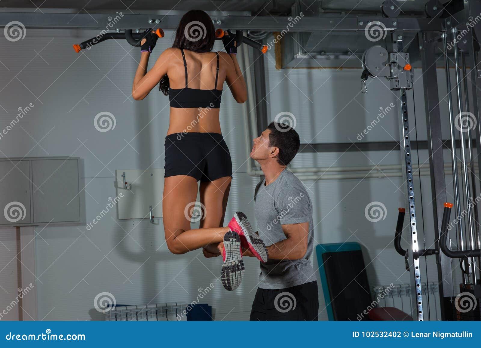 Тренировки женщины на турнике с инструктором