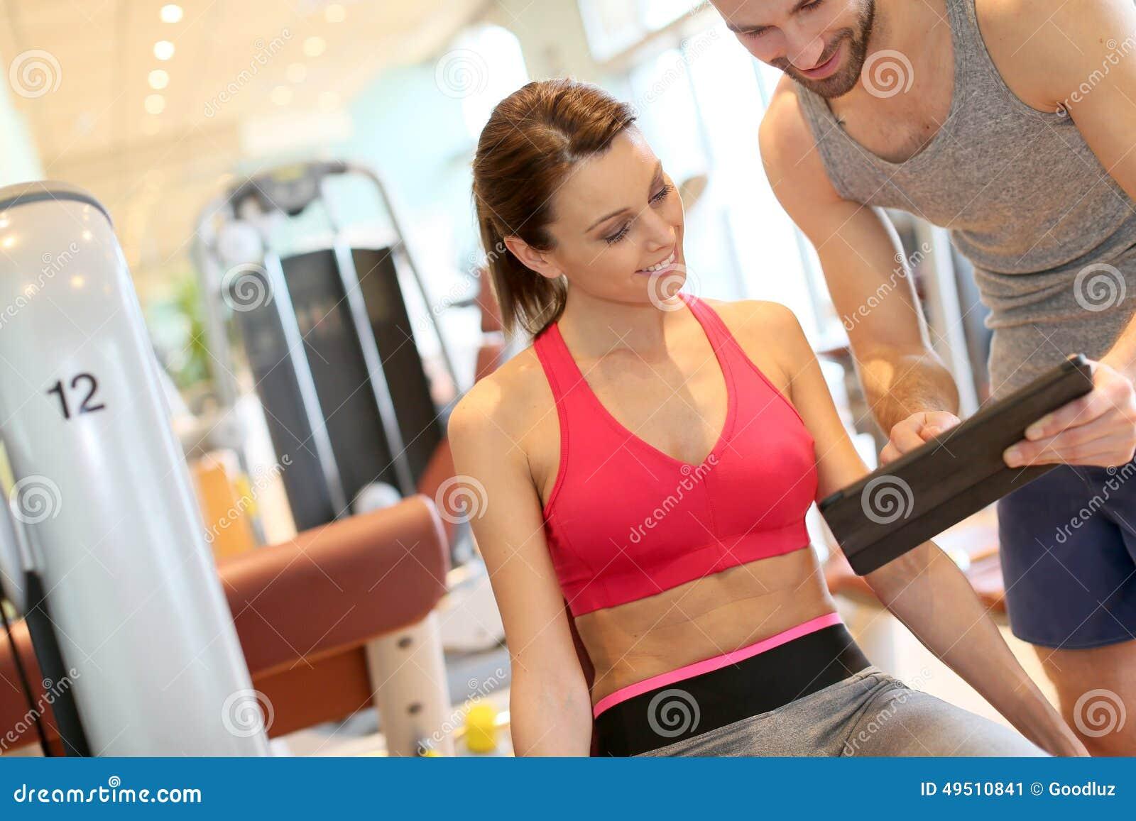 Тренируйте направлять девушку фитнеса через разрабатывая программу
