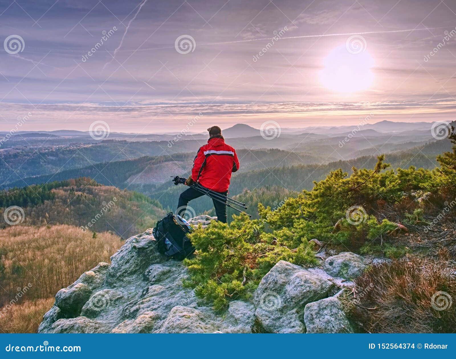 Тренога владением человека Hiker восхищая сногсшибательную горную цепь