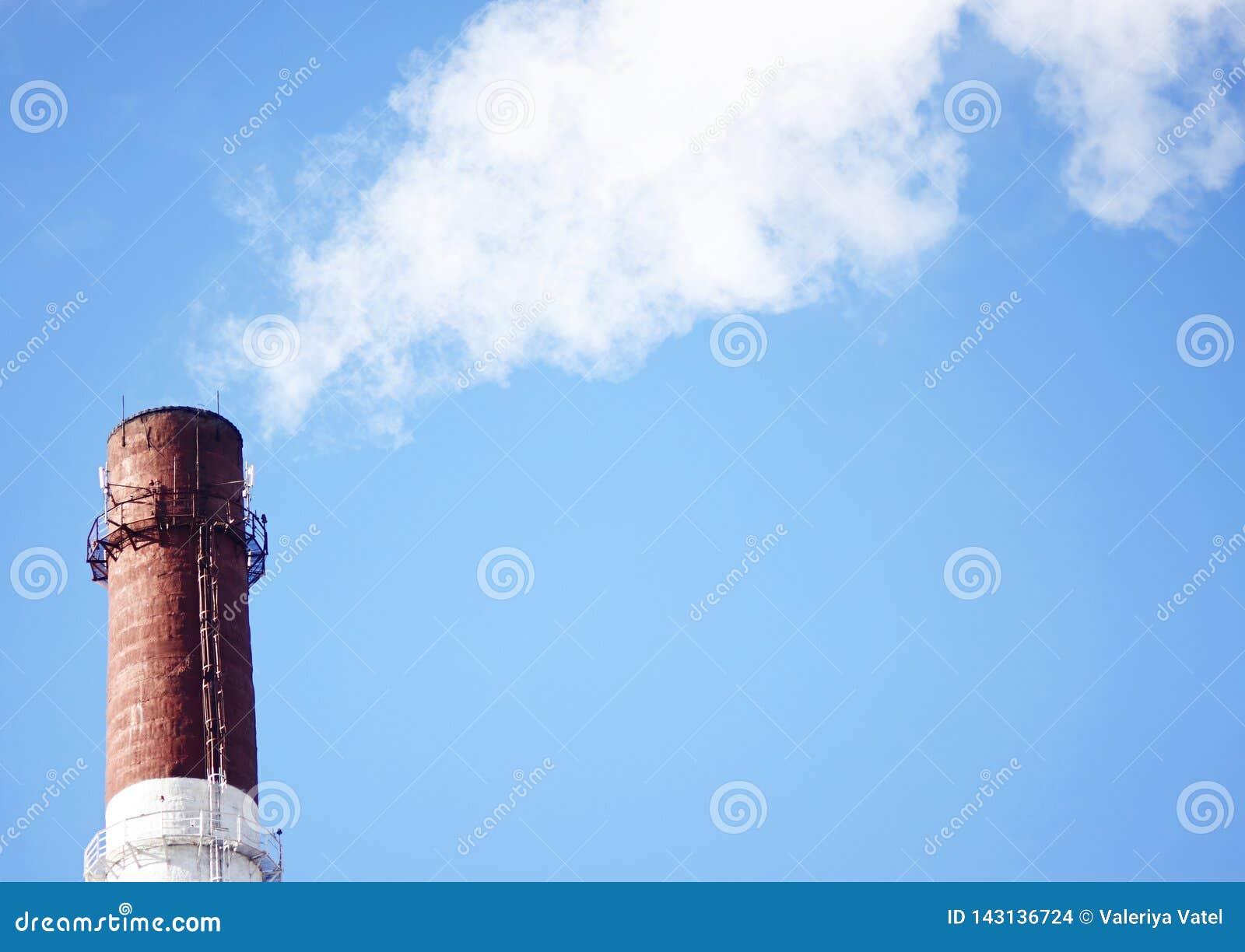 Труба фабрики испуская отработанные газы в небо