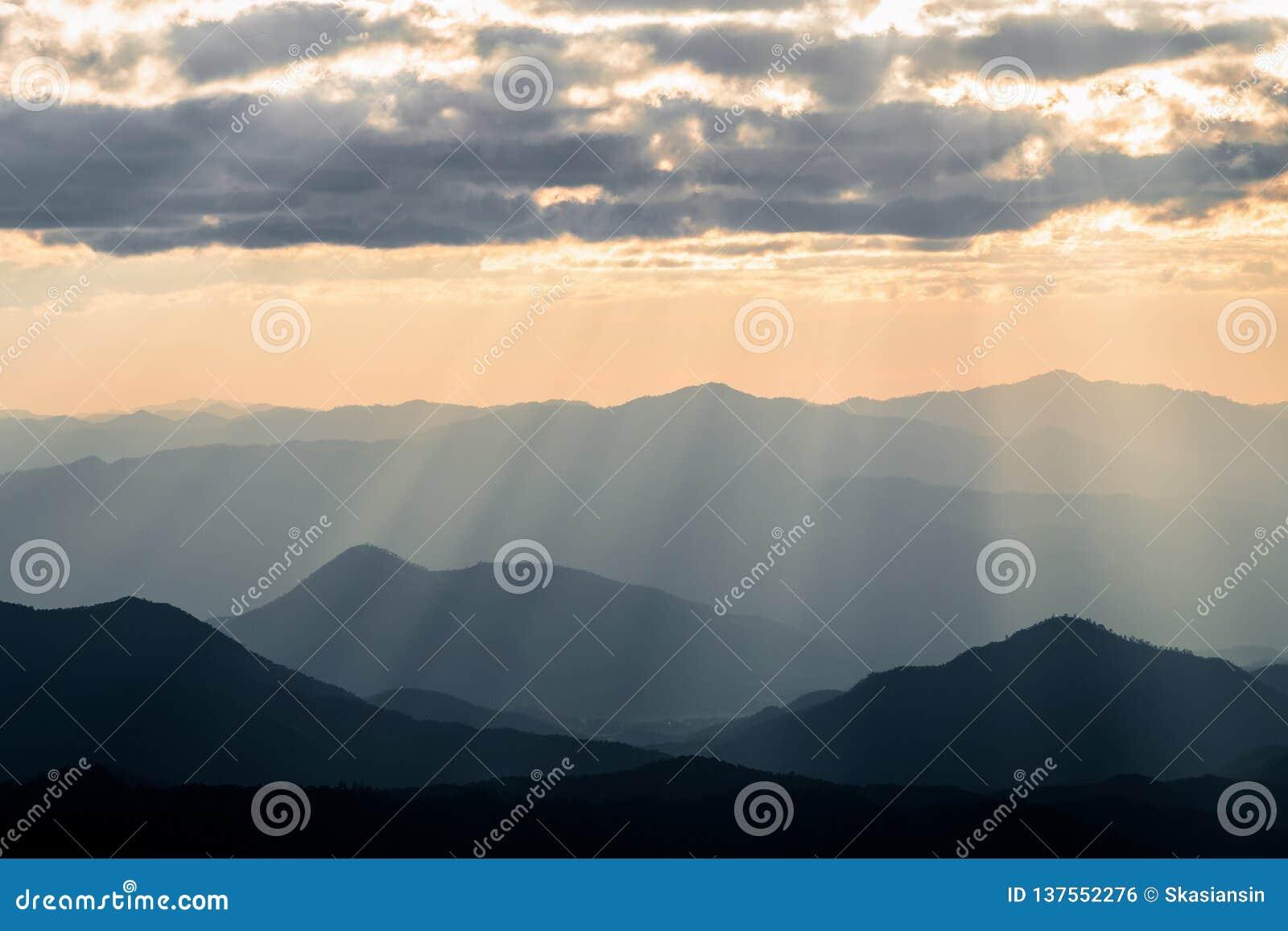 Туманная горная цепь с драматическим небом захода солнца