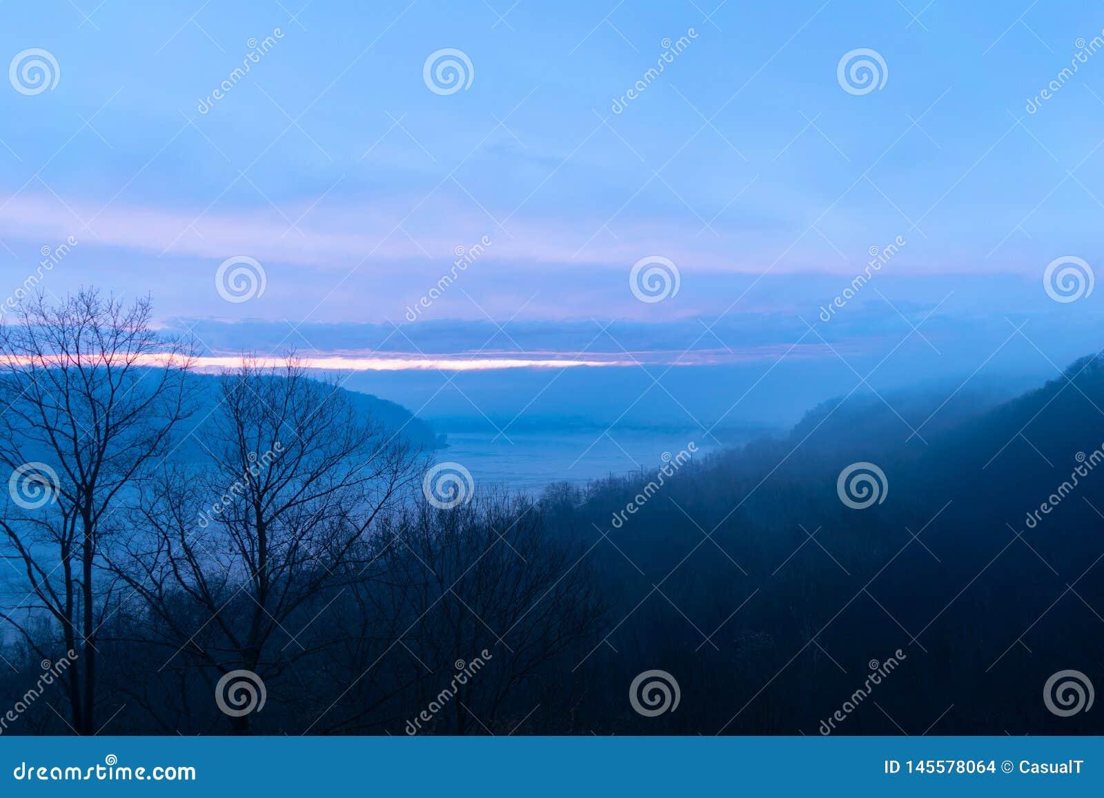 Туманная и унылая съемка загиба в Реке Susquehanna, пока мычка захода солнца выходит сквозь отверстие толстые облака