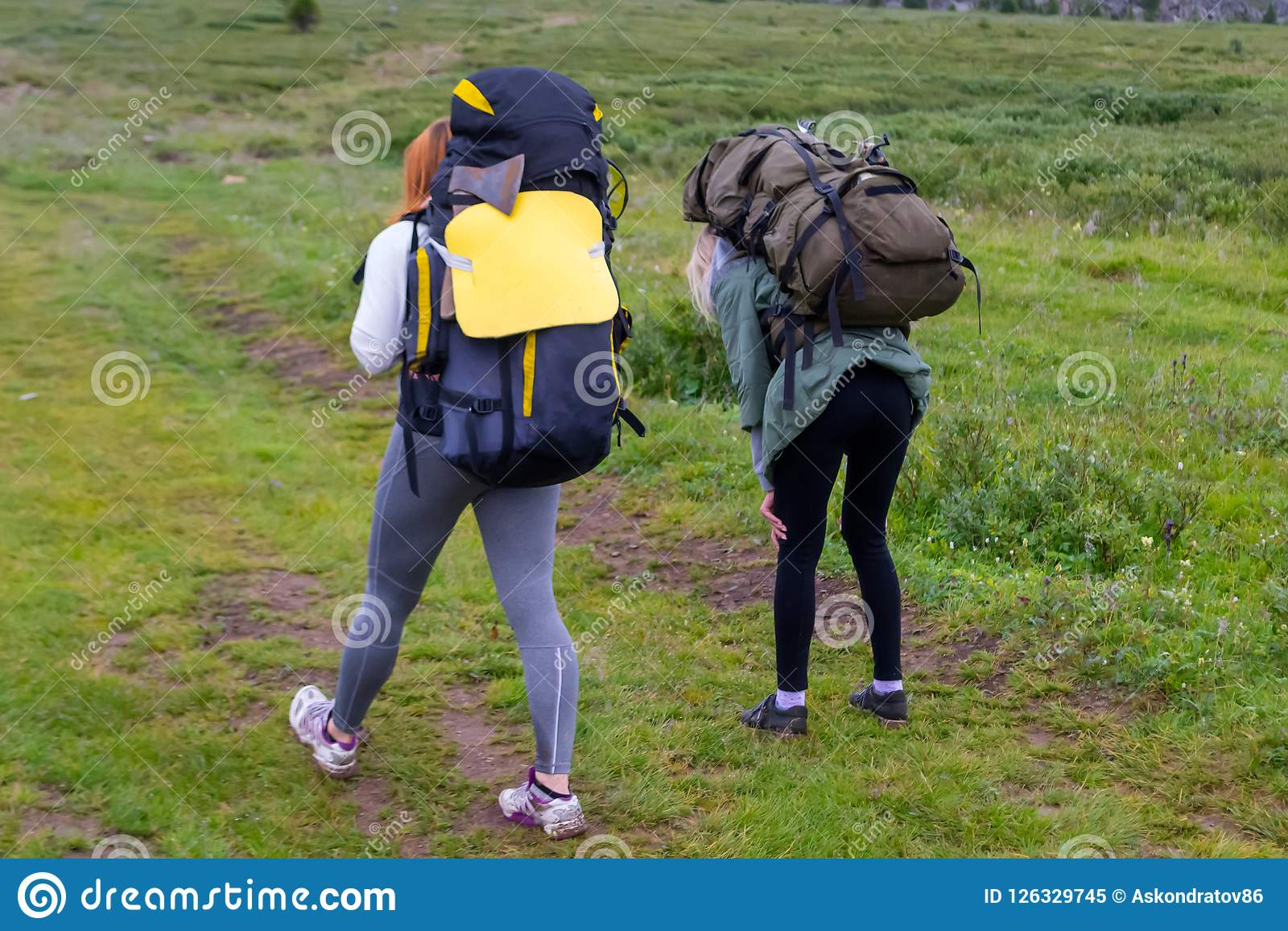 2 туриста девушек с рюкзаками идут на дорогу покрытую с st