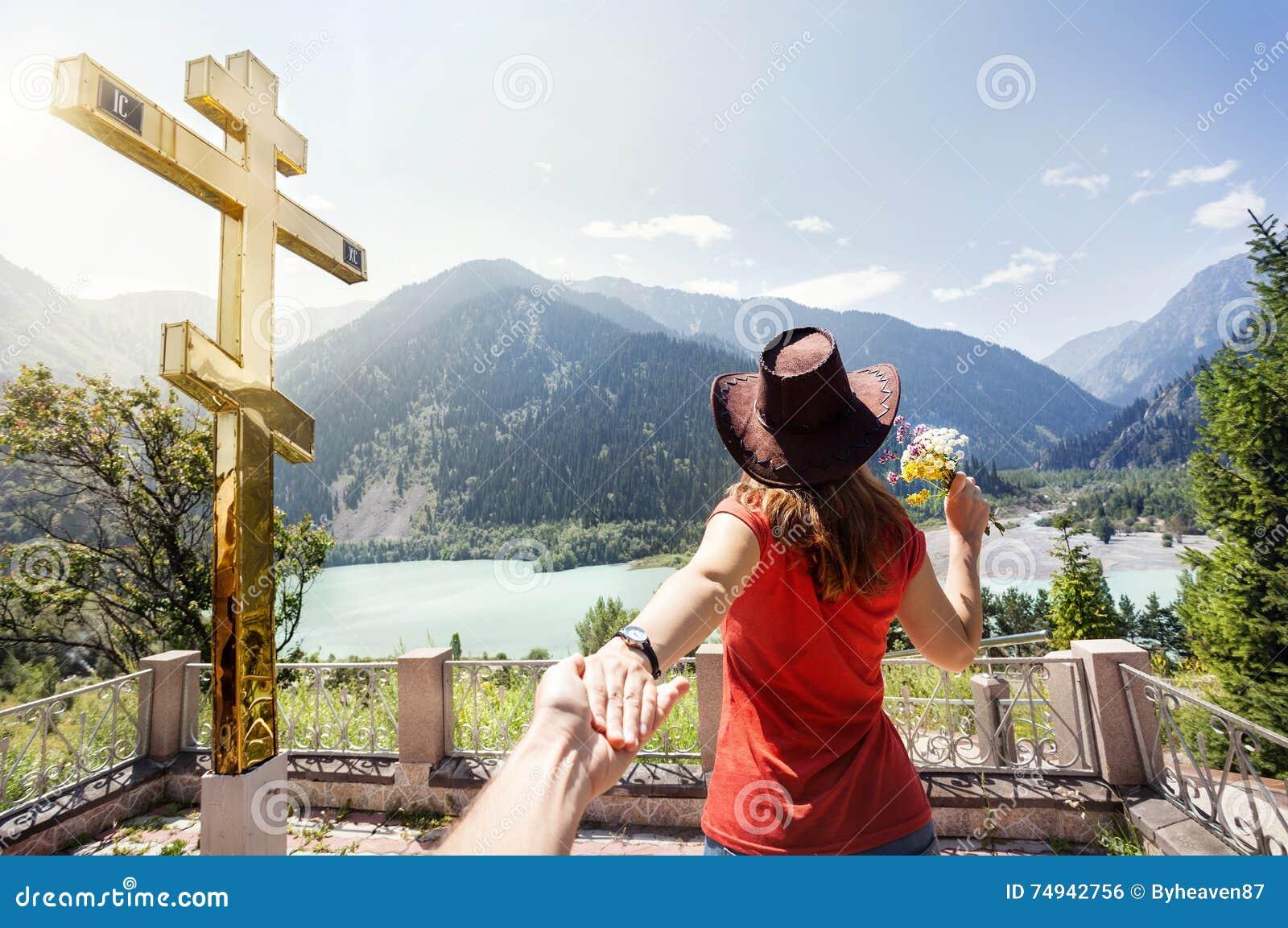 Туристская женщина на горах приближает к золотому кресту