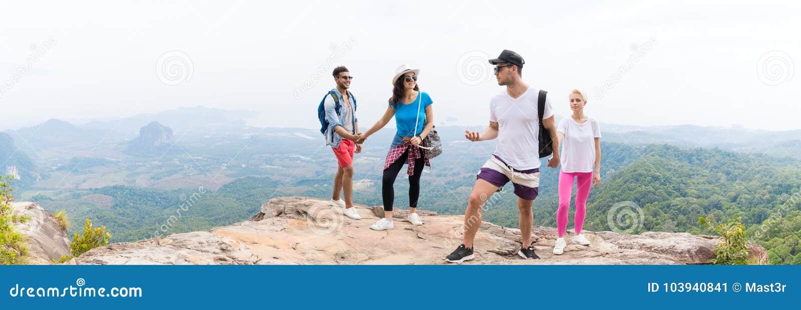 2 туристских пары с рюкзаком на говорить горы верхний над красивым взглядом панорамы ландшафта