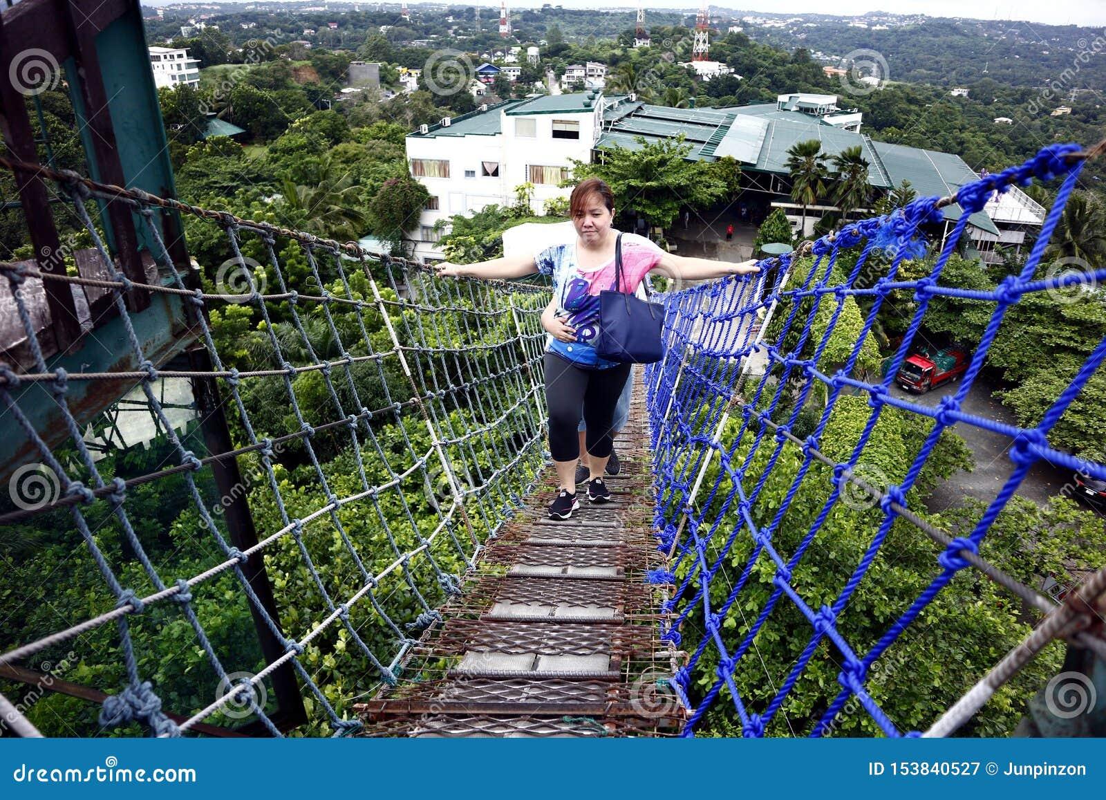 Туристы и посетители взбираются к верхней части палубы просмотра 360 градусов используя вися мост