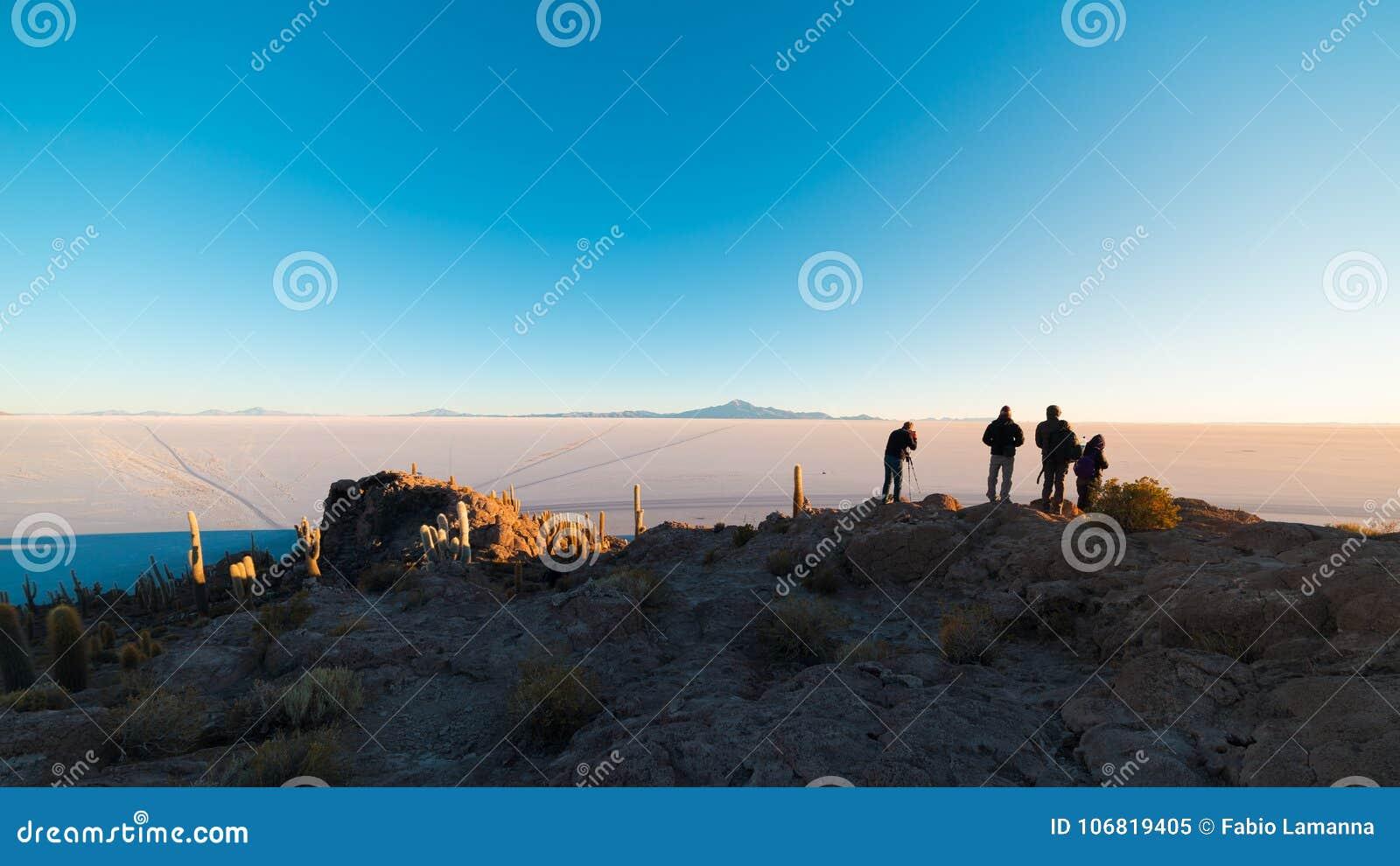 Туристы наблюдая восход солнца на квартире соли Uyuni, назначении перемещения в Боливии Широкоформатная съемка от саммита Incahua