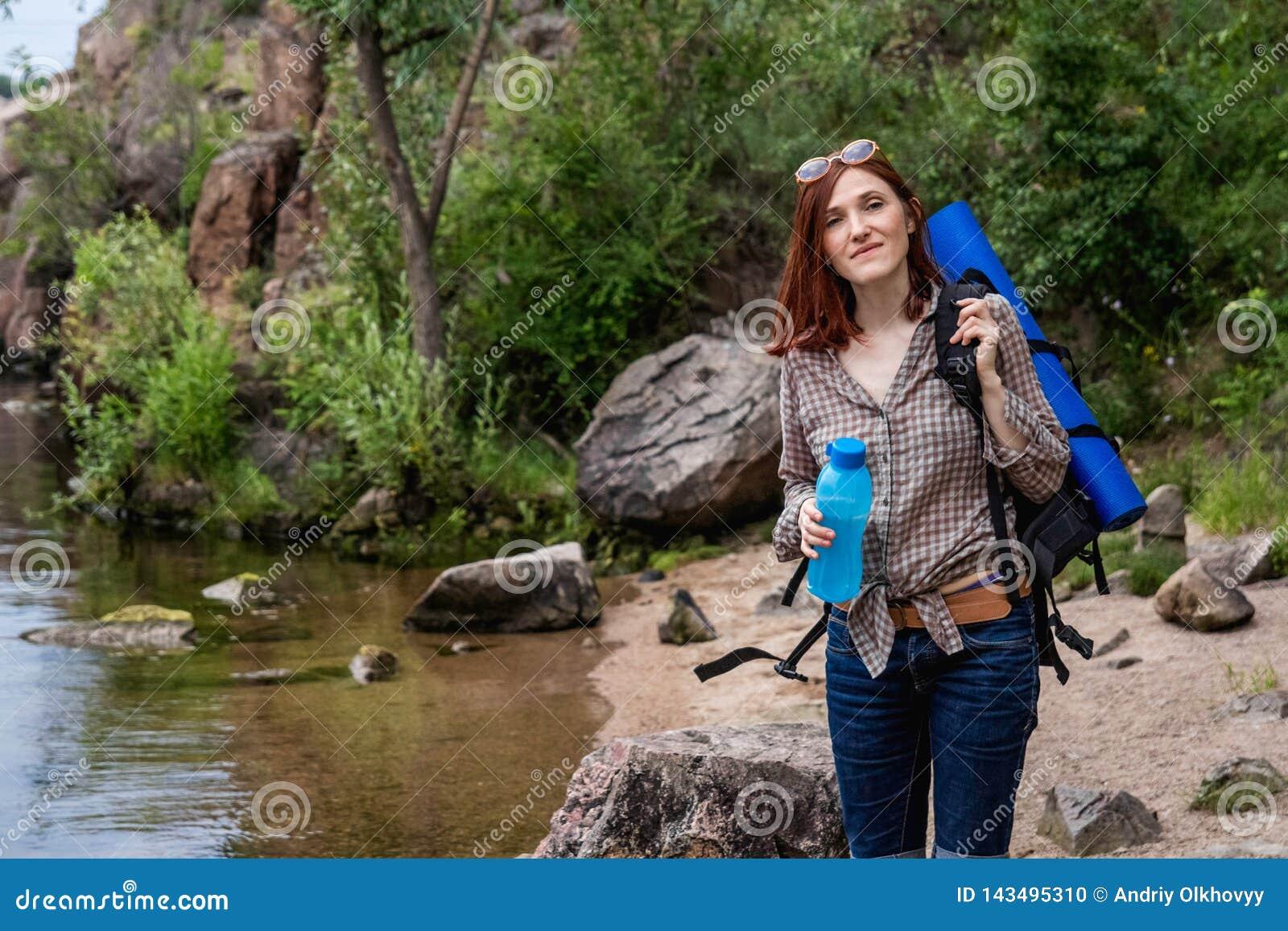 Турист женщины с прогулкой рюкзака в походе против предпосылки красивого пейзажа горы вдоль реки горы