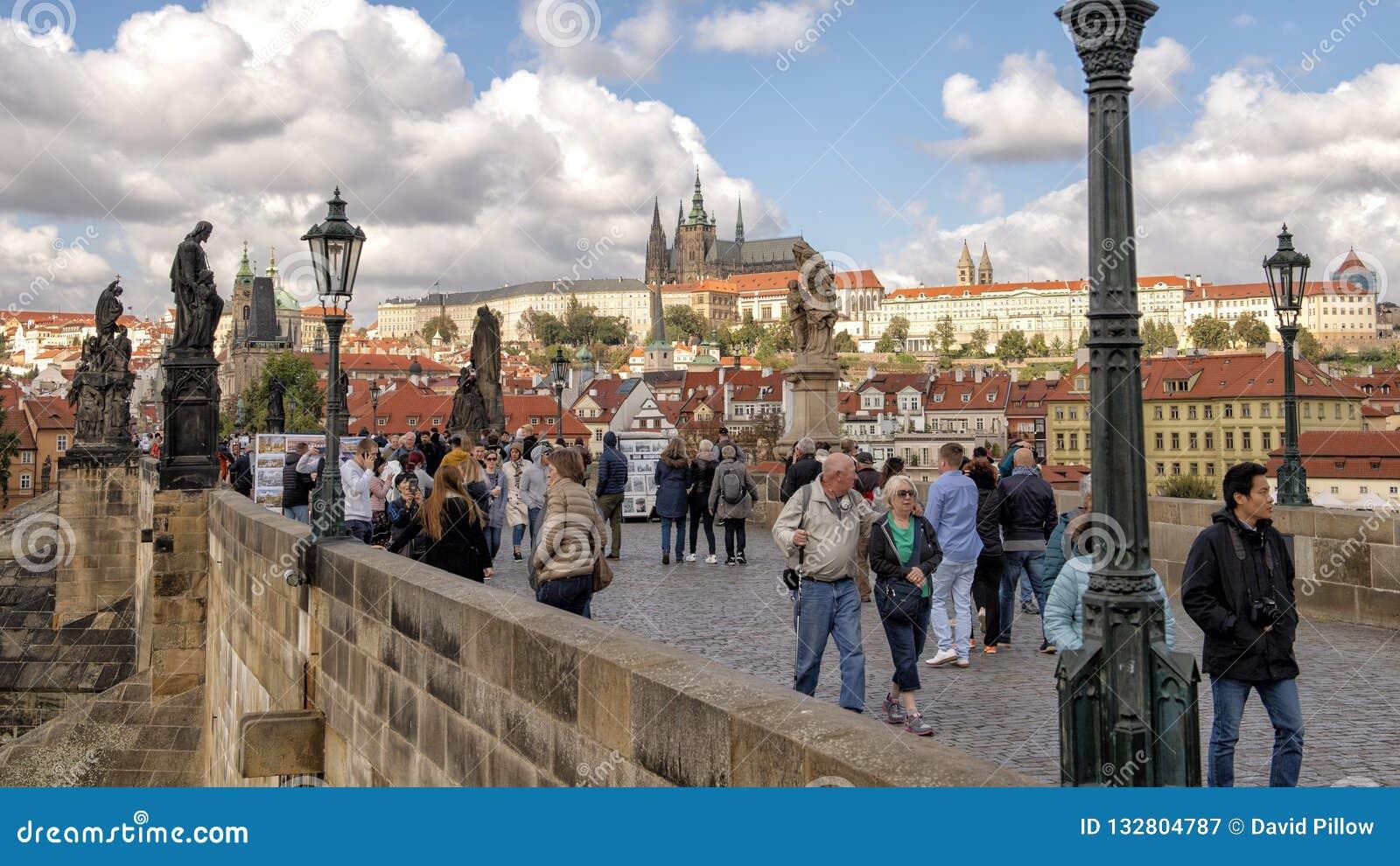 Турист заполнил Карлов мост с ним известные скульптуры, с замком Праги на заднем плане, Прага, чехия