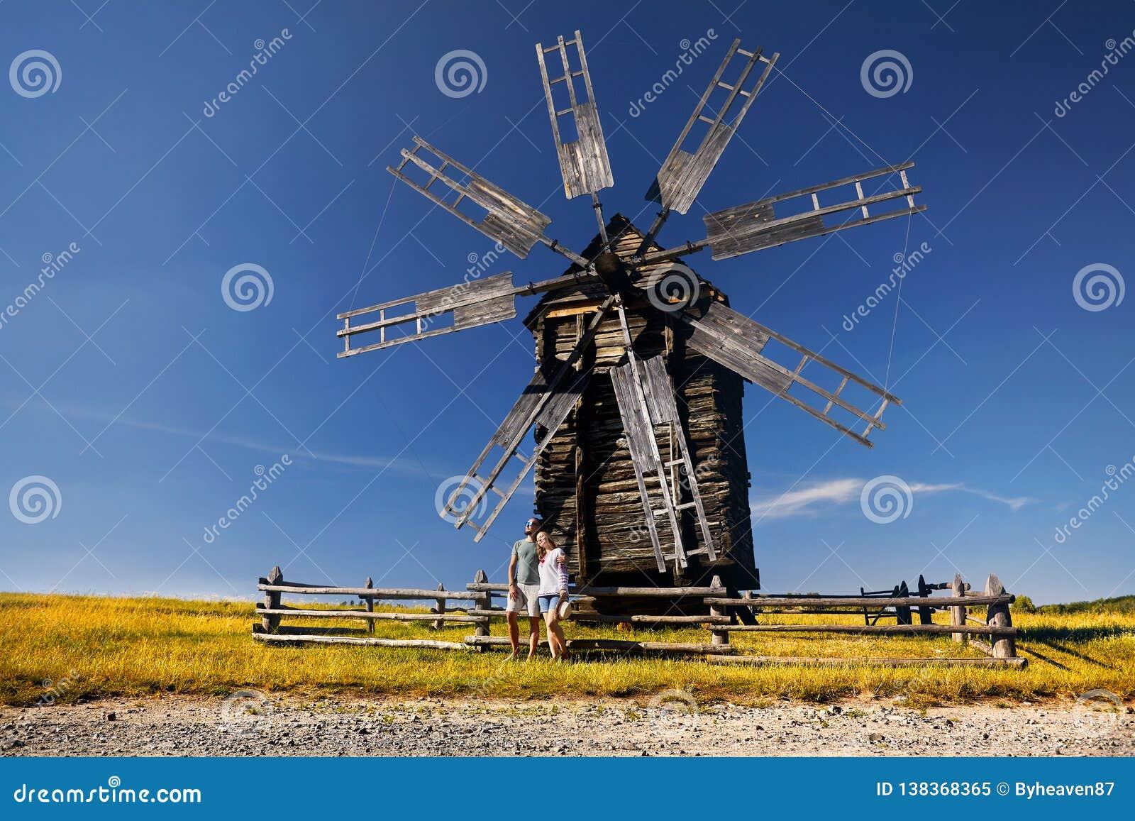 Турист около деревянной мельницы ветра