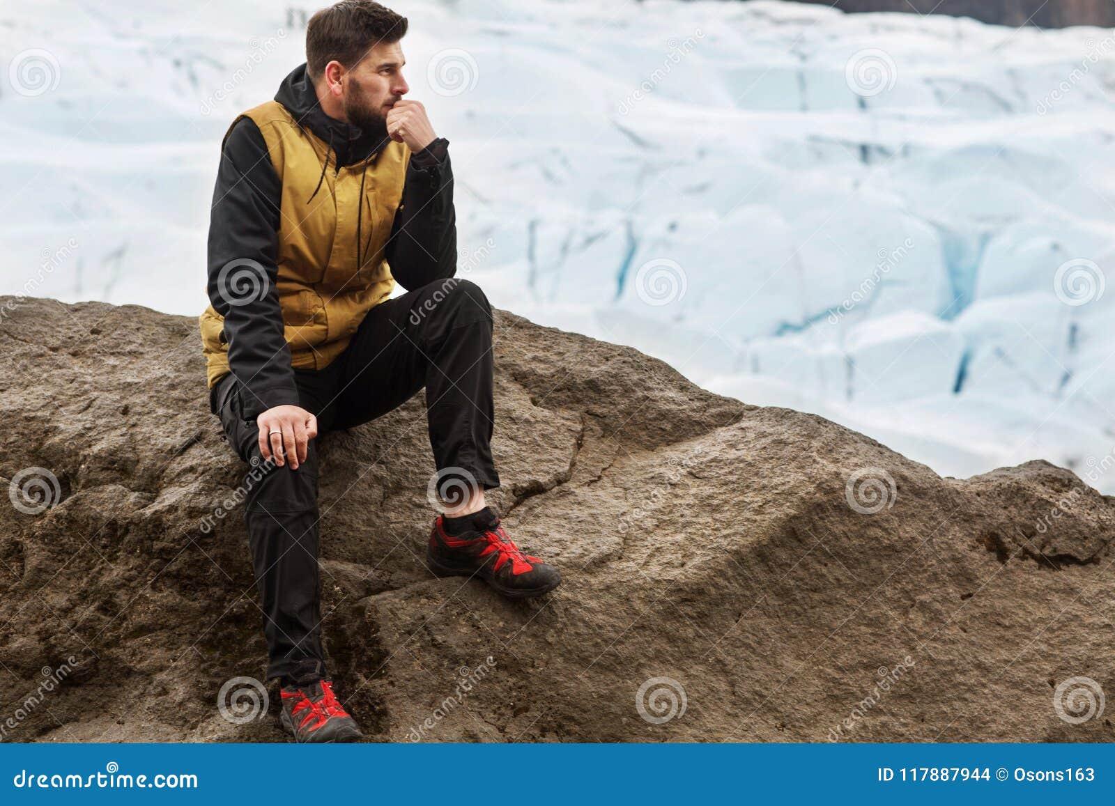 Турист сидит около айсберга ледника в Исландии