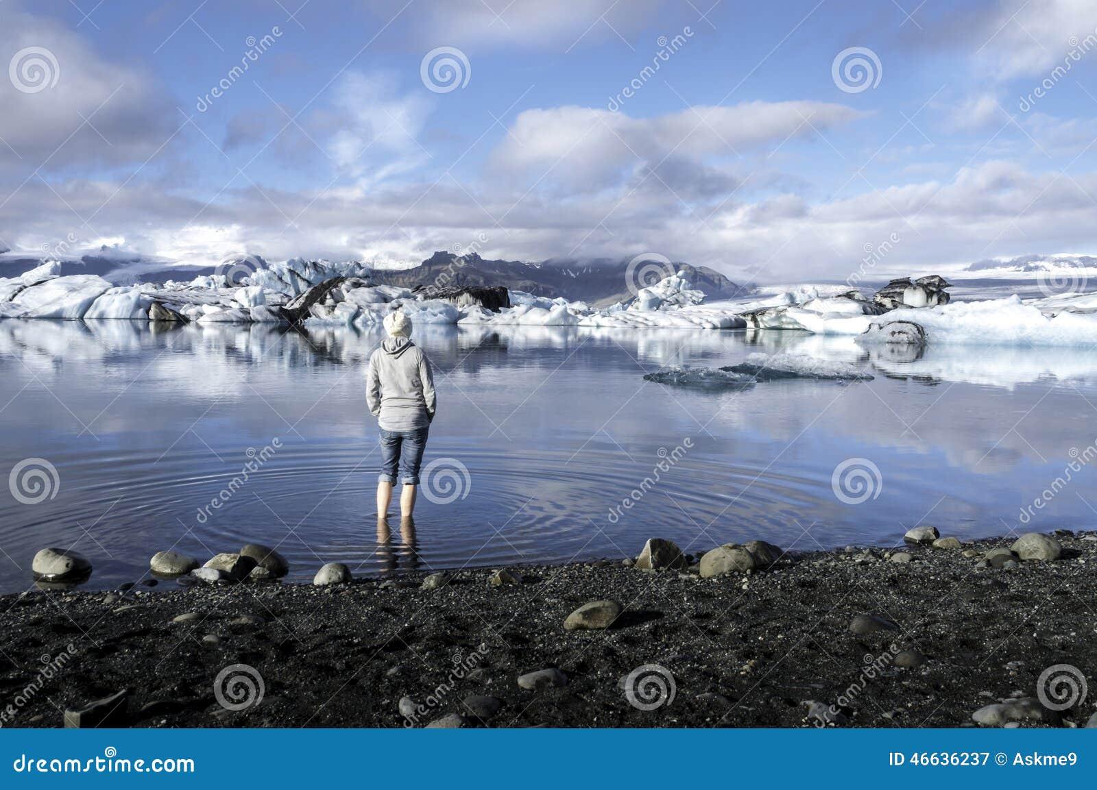Турист смотря Jokulsarlon, лагуну, Исландию
